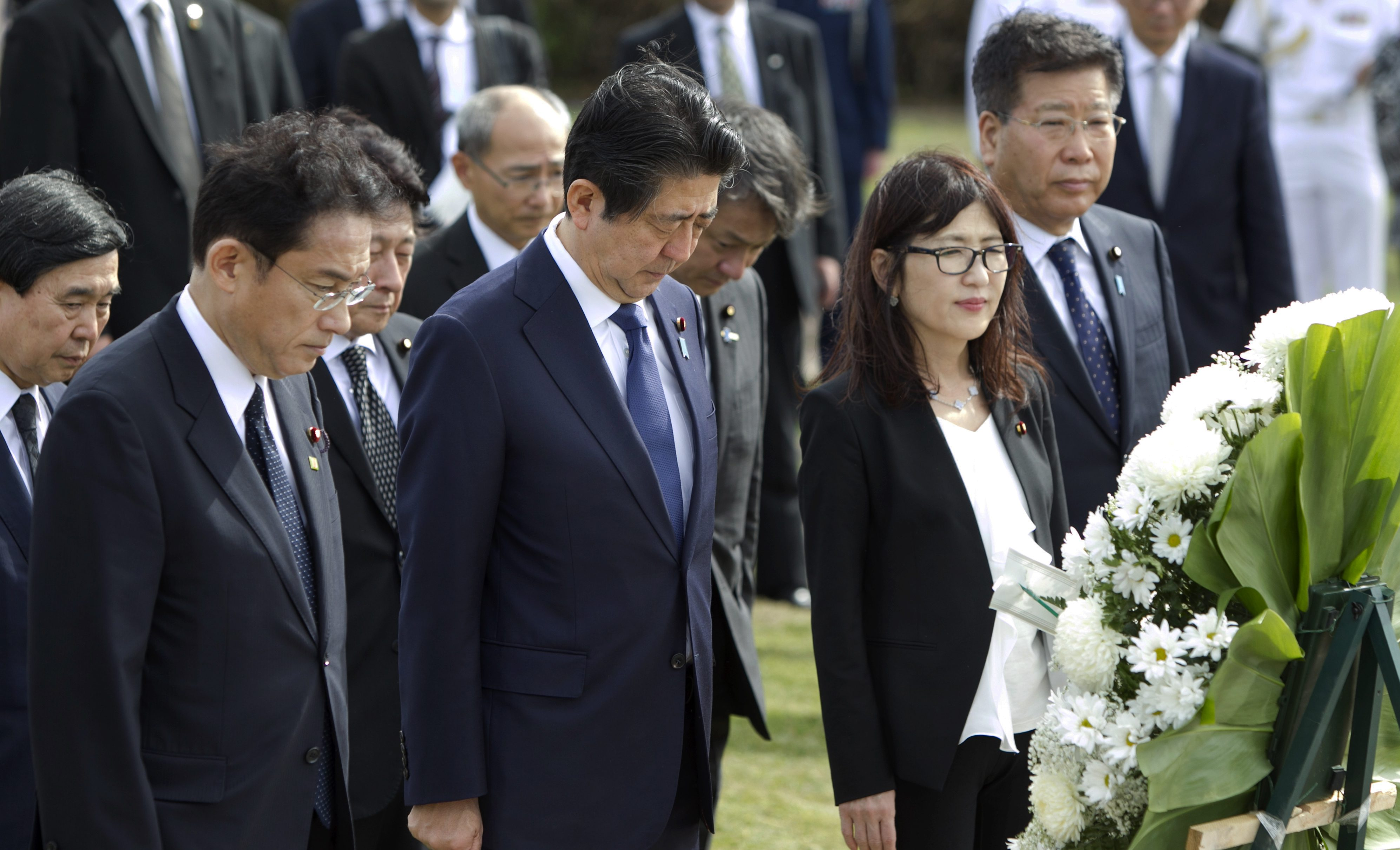 From left, Sal Miwa, of the Japan-America Society of Hawaii, Japanese Prime Minister Shinzo Abe, Japanese Defense Minister Tomomi Inada, and Japan's Deputy Chief Cabinet Secretary Koichi Hagiuda bow at the Ehime Maru Memorial at Kakaako Waterfront Park, Monday, Dec. 26, 2016, in Honolulu. The memorial is dedicated to the victims of a 2001 deadly collision off the coast of Hawaii between the Ehime Maru, a fisheries training vessel, and a U.S. naval submarine. Abe plans to visit Pearl Harbor with U.S. President Barack Obama Tuesday.