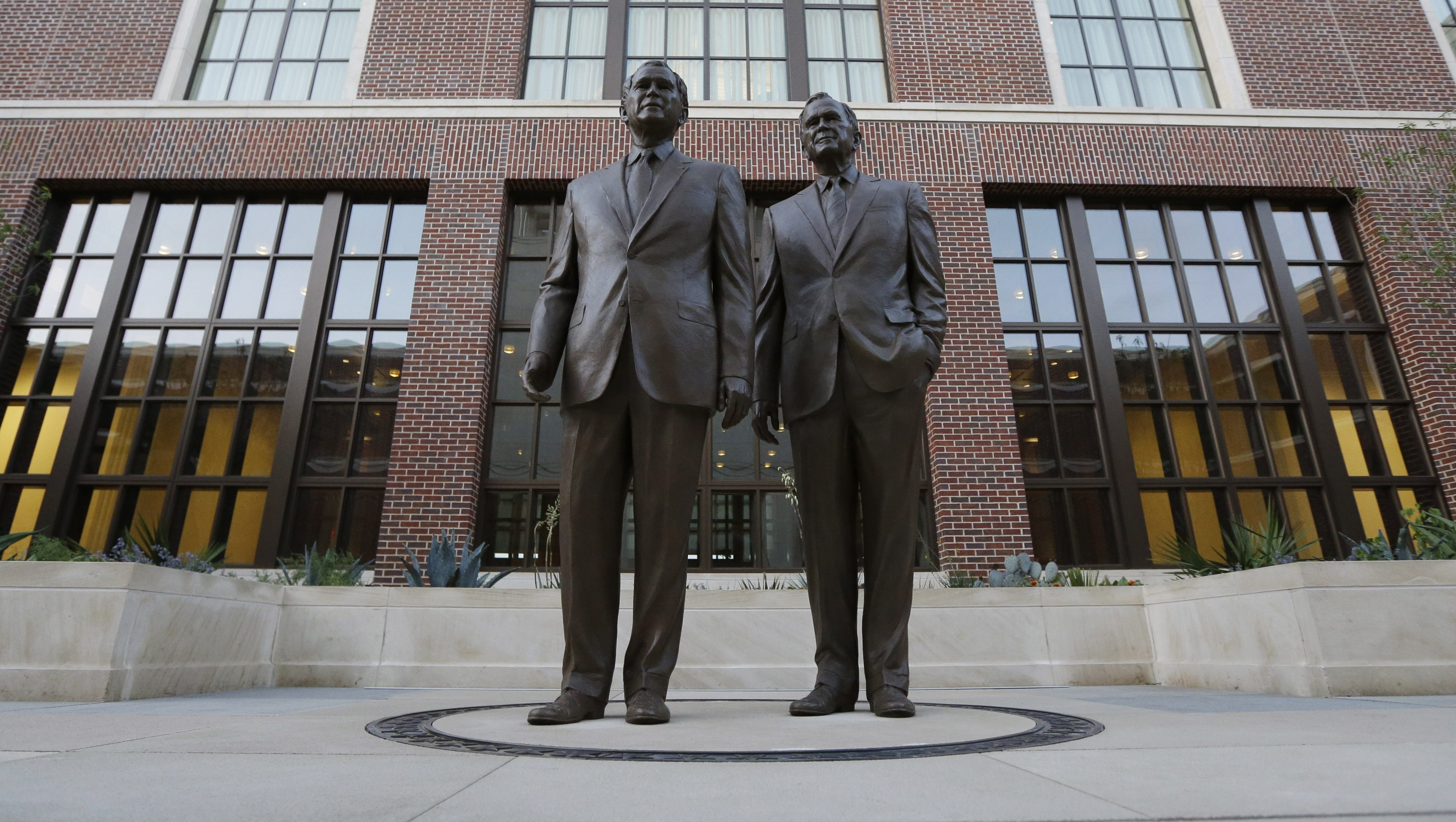 Statues of former Presidents George W. Bush, left and George HW Bush are seen during a tour of the George W. Bush Presidential Center Wednesday, April 24, 2013, in Dallas.  More than 8,000 people are expected to attend the invitation-only dedication of the center, Thursday, April 25, which will house the presidential library and museum along with the 43rd president's policy institute. It opens to the public on May 1. (AP Photo/David J. Phillip)