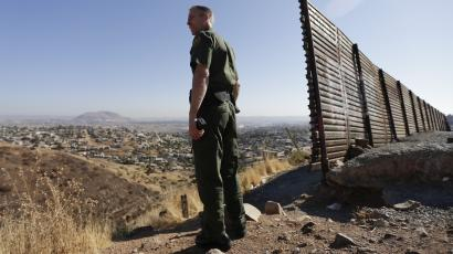 In this June 13, 2013 file photo, US Border Patrol agent Jerry Conlin looks out over Tijuana, Mexico, behind, along the old border wall along the US - Mexico border, where it ends at the base of a hill in San Diego. After dropping during the recession, the number of immigrants crossing the border illegally into the U.S. appears to be on the rise again, according to a report released Monday, Sept. 23, 2013 by Pew Research Center's Hispanic Trends Project.