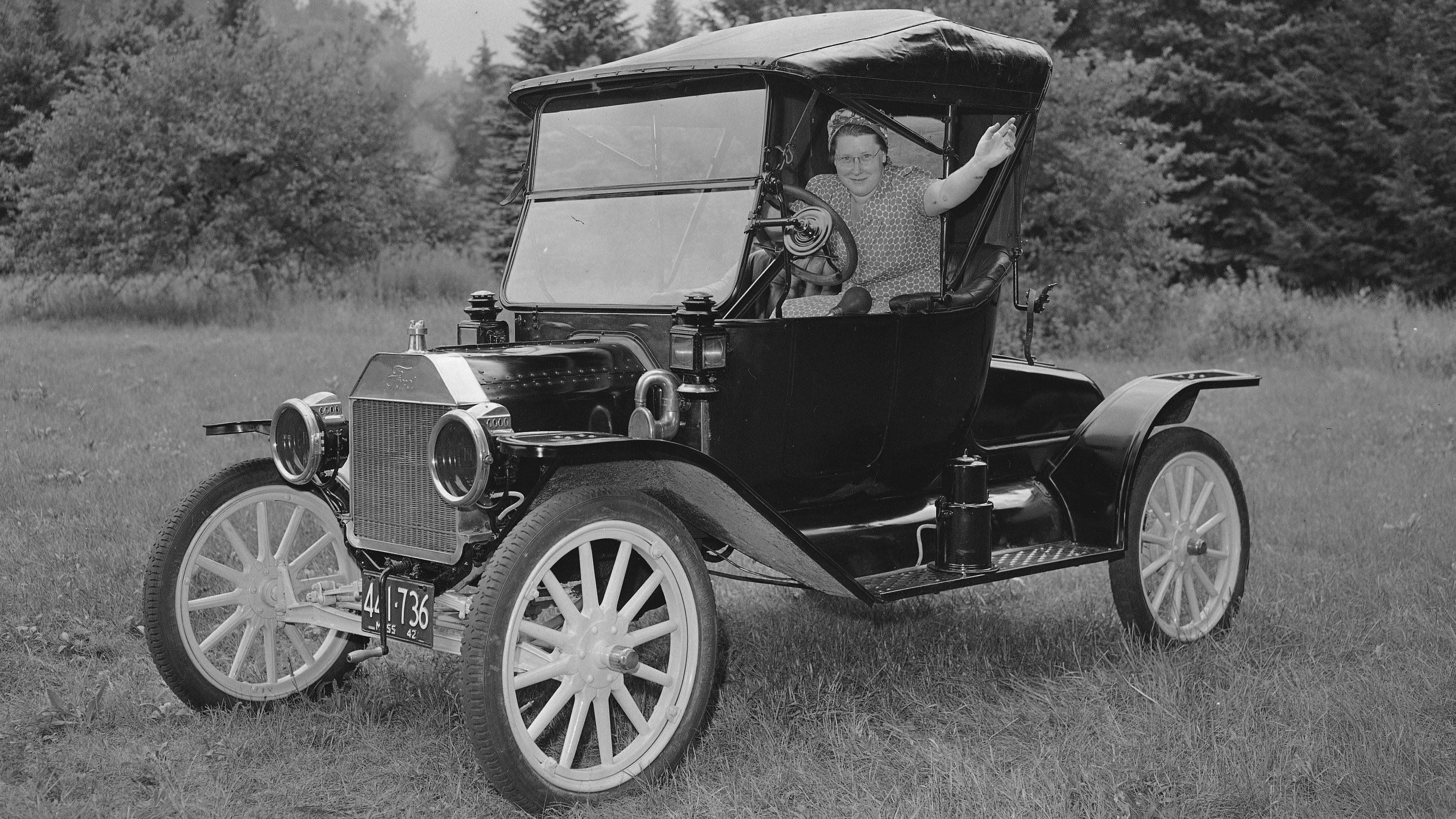 Mrs. Mildred C. Reniff of Ashfield, Mass, waves good-bye as she starts a test flight in her vintage 1914 Model T. Ford, August 4, 1944. Mrs. Reniff heeded advice of Federal Agencies to make cars last as long as possible and had it put in tip top shape. Tank on running Board mixes Carbide and water to form gas for headlights. (AP Photo)