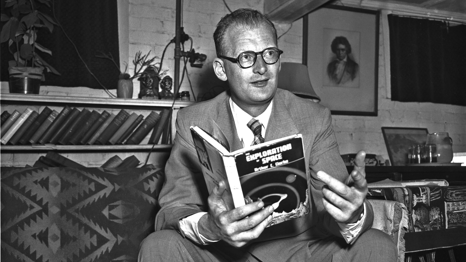 "**FILE**Science fiction author Arthur C. Clarke holds a copy of his book, ""Exploration of Space"" at a home in Washington, D.C., in this June 9, 1952 file photo. (AP Photo/File)"