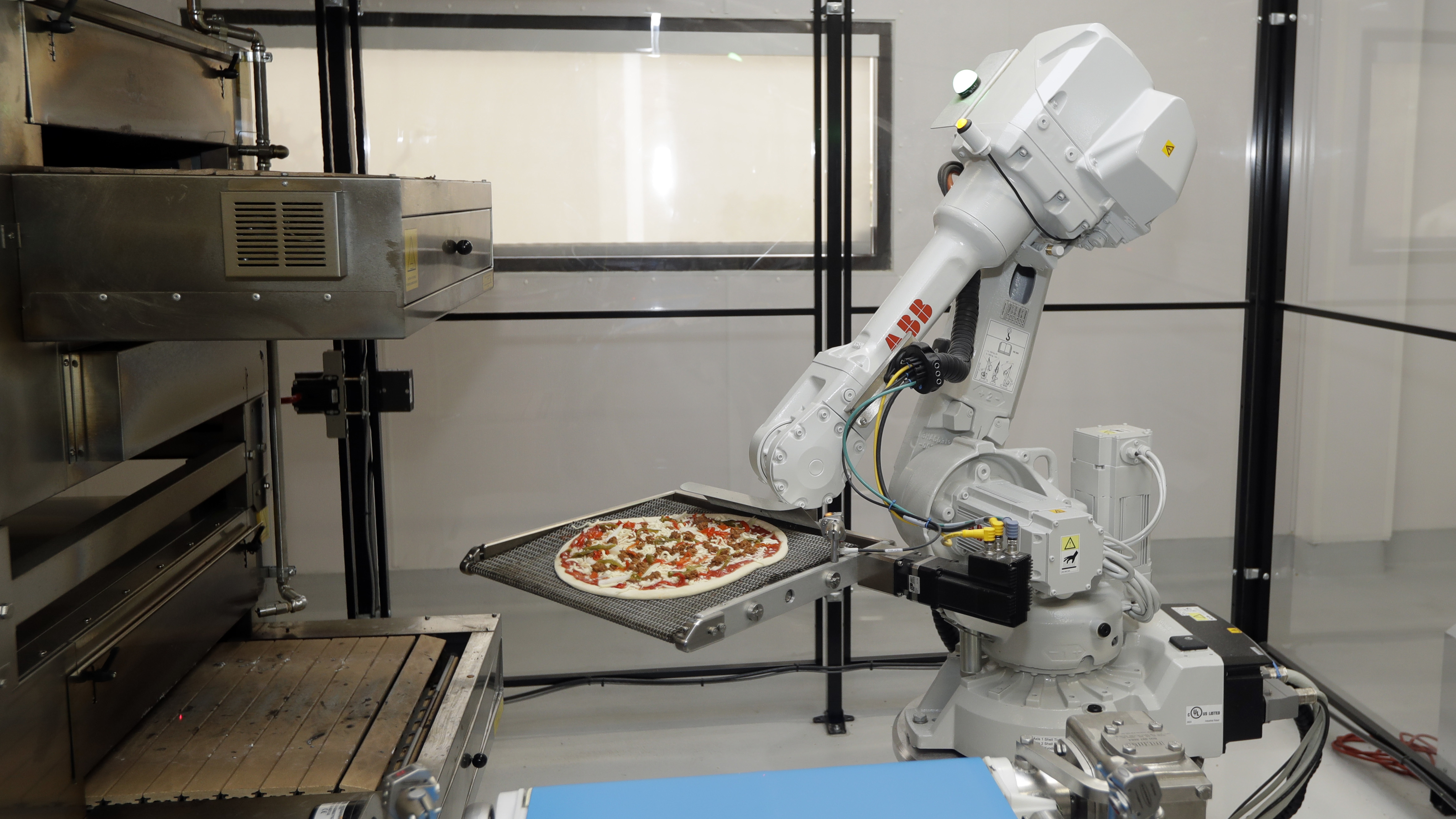 In this Monday, Aug. 29, 2016 photo, a robot places a pizza into an oven at Zume Pizza in Mountain View, Calif. The startup, which began delivery in April, is using intelligent machines to grab a slice of the multi-billion-dollar pizza delivery market. Zume is one of a growing number of food-tech firms seeking to disrupt the restaurant industry with software and robots that let them cut costs, speed production and improve worker safety. (AP Photo/Marcio Jose Sanchez)