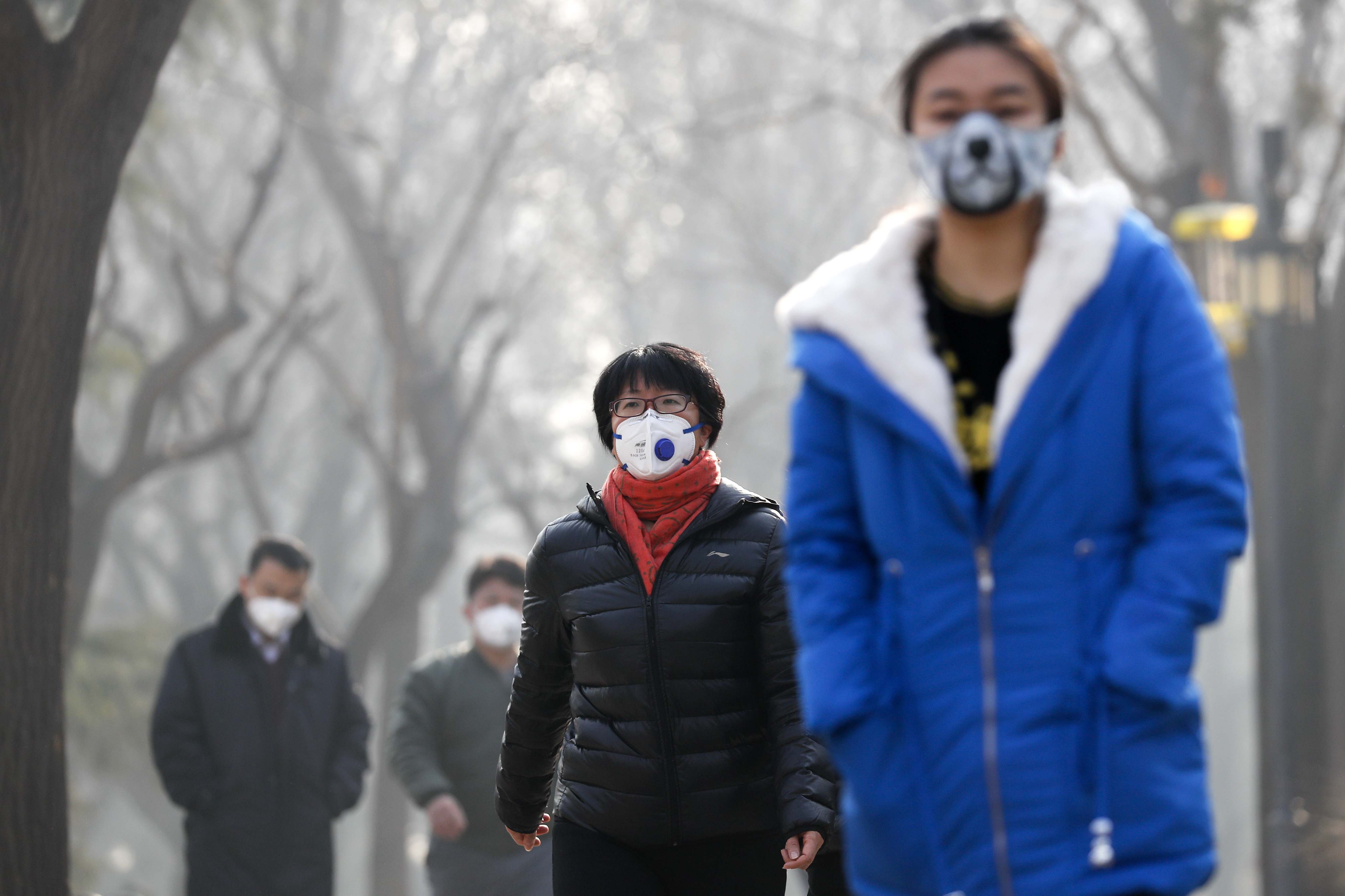 """Chinese people wearing masks for protection against pollution walk at Ritan Park shrouded by heavy smog in Beijing, Monday, Dec. 19, 2016. Chinese cities are limiting the number of cars on roads and have temporarily shut down factories to cut down pollution during a national """"red alert"""" for smog. (AP Photo/Andy Wong)"""