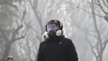 """A man wearing a mask for protection against pollution exercise at Ritan Park during a heavily polluted day in Beijing, Monday, Dec. 19, 2016. Chinese cities are limiting the number of cars on roads and have temporarily shut down factories to cut down pollution during a national """"red alert"""" for smog. (AP Photo/Andy Wong)"""