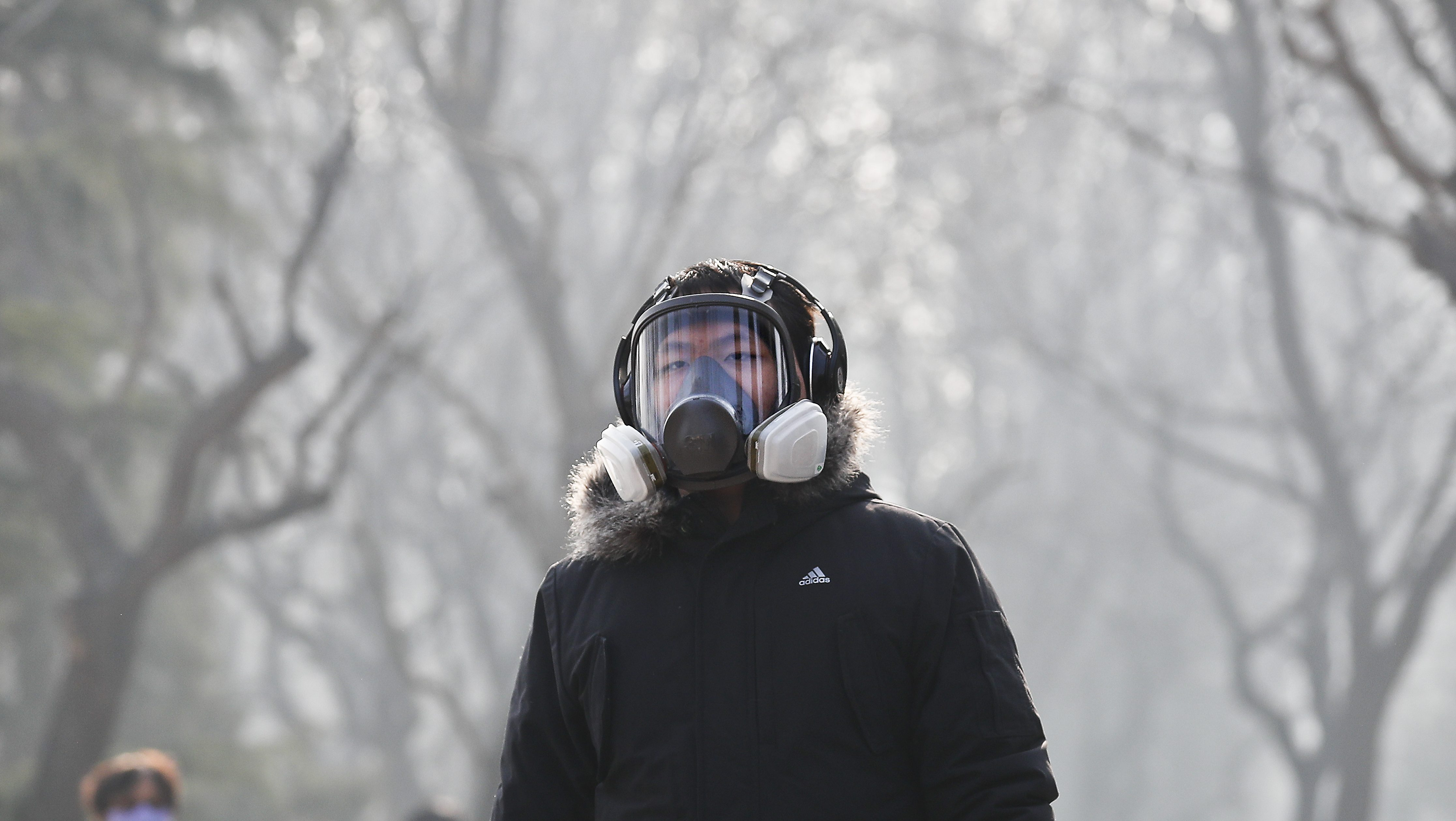 "A man wearing a mask for protection against pollution exercise at Ritan Park during a heavily polluted day in Beijing, Monday, Dec. 19, 2016. Chinese cities are limiting the number of cars on roads and have temporarily shut down factories to cut down pollution during a national ""red alert"" for smog. (AP Photo/Andy Wong)"