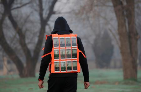 Artist Liu Bolin wearing a vest with 24 mobile phones walks in smog as he live broadcasts air pollution in the city on the fourth day after a red alert was issued for heavy air pollution in Beijing, China, December 19, 2016. REUTERS/Jason Lee - RTX2VLZ9