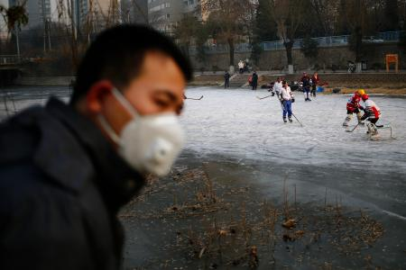 A Chinese man wears a mask while watching people play ice hockey on a frozen river while haze hangs over downtown Beijing city, China, 16 December 2016. Officials in China's capital Beijing issued a red alert for air pollution, which is expected to last until 21 December. EPA/WU HONG