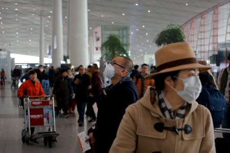 "A man wearing a mask for protection against air pollution looks at a flight information board at the Beijing Capital International Airport as the capital of China is shrouded by heavy smog on Dec.21, 2016. Beijing and much of industrial northern China are in the midst of a ""red alert,"" the highest level in China's four-tiered pollution warning system. The alert has affected 460 million people, according to Greenpeace East Asia, which calculated that about 200 million people were living in areas that had experienced levels of air pollution more than 10 times above the guideline set by the World Health Organization. (AP Photo/Andy Wong)"