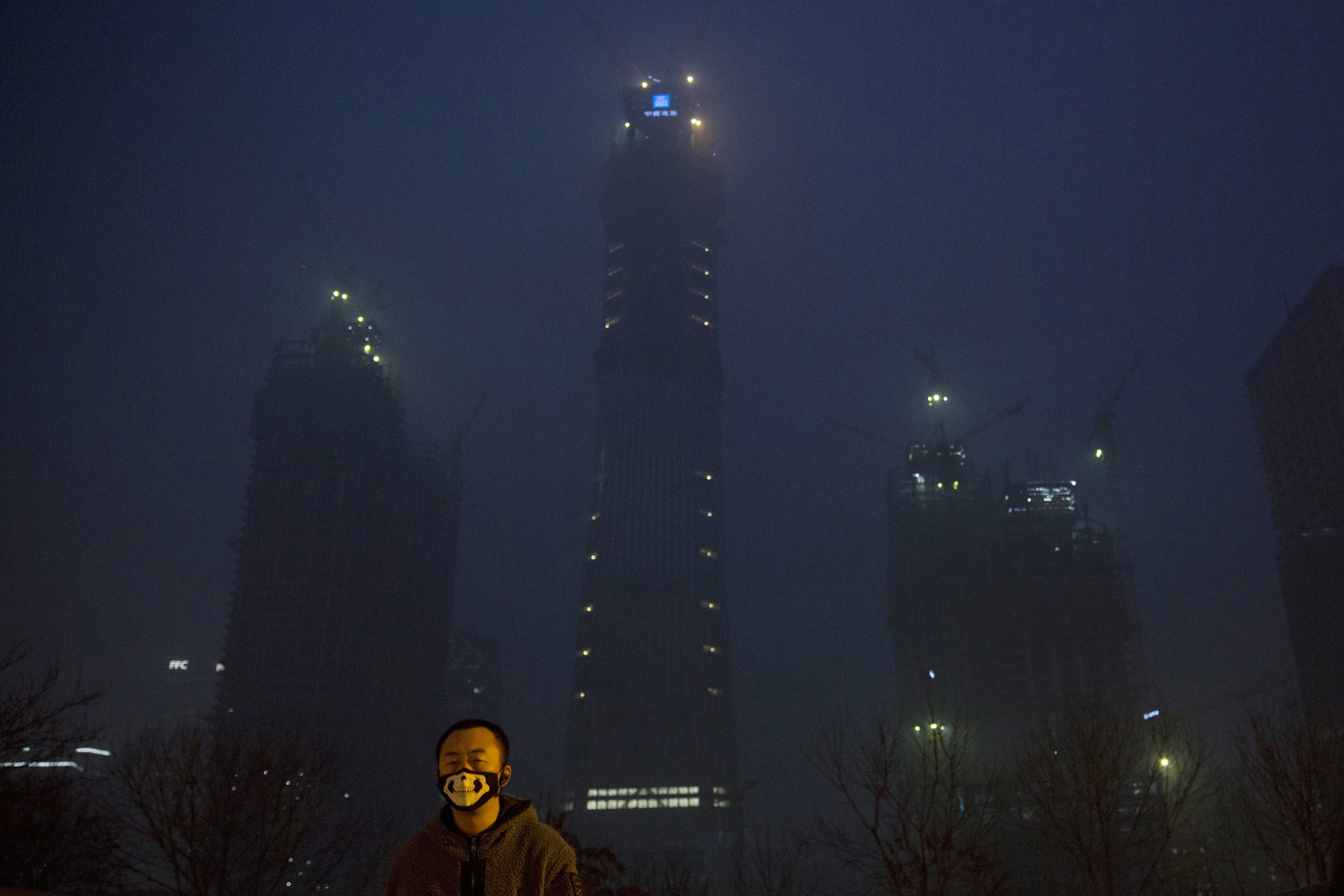 A man wears a mask with a skeleton design near the smoggy night scene of the Central Business District under construction in Beijing, China on Dec.21, 2016. Chinese weather forecasters and state media say the dense, gray smog that has smothered much of China, closing schools and grounding planes, may finally soon give way. (AP Photo/Ng Han Guan)