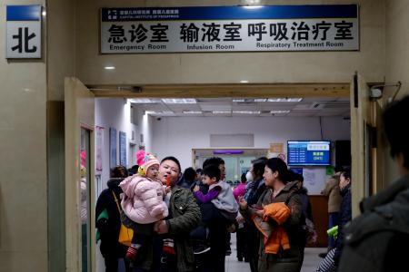 Parents with their children wait at a holding room of a children's hospital in Beijing, Sunday, Dec. 18, 2016. A smog-shrouded Chinese city canceled airline flights Sunday due to poor visibility and many parents took children to hospitals on the second day of a pollution alert across the country's north. (AP Photo/Andy Wong)