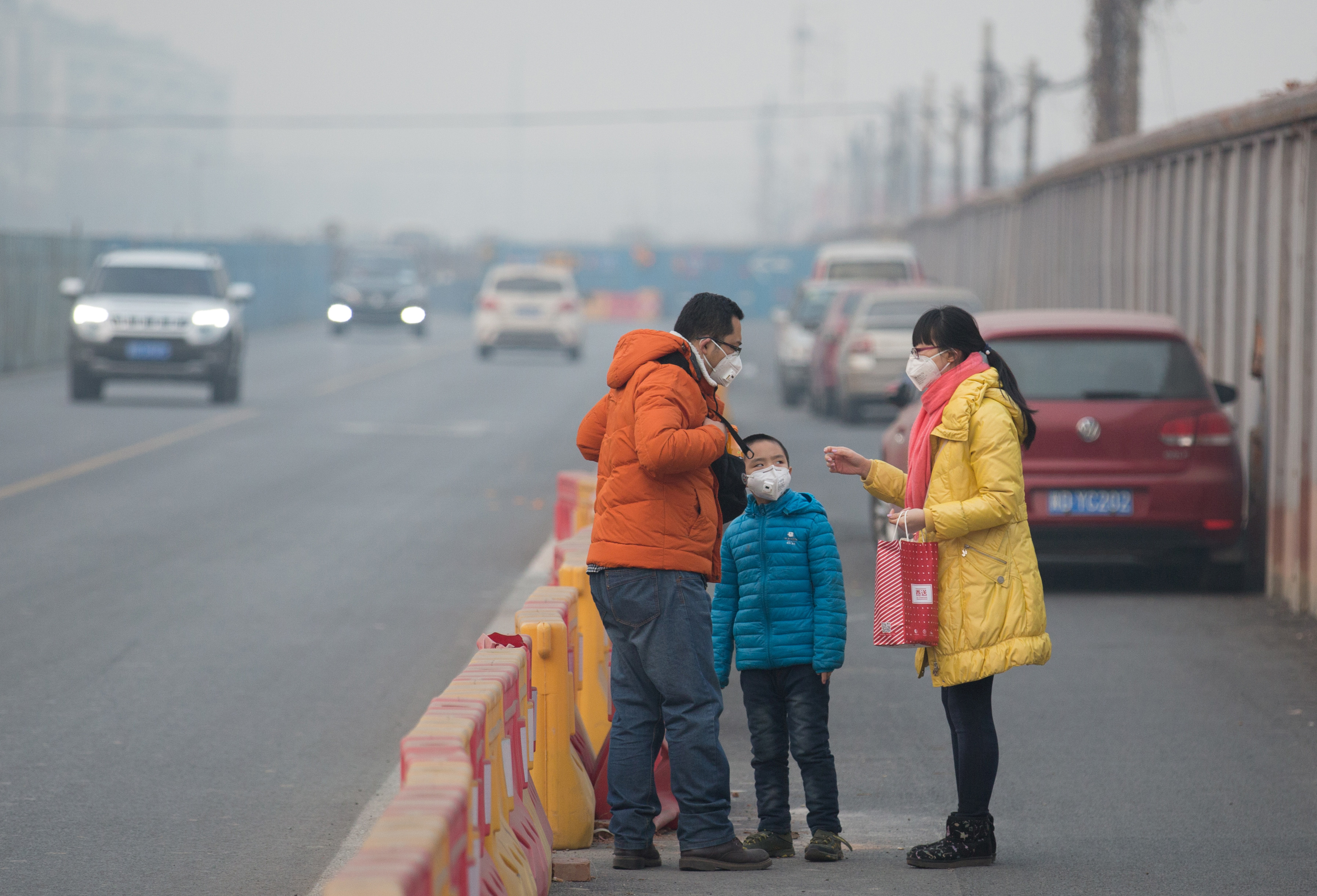 People wearing masks stand in smog during a heavily polluted day in Beijing, China, December 17, 2016. Picture taken December 17, 2016. China Daily/via REUTERS ATTENTION EDITORS - THIS PICTURE WAS PROVIDED BY A THIRD PARTY. EDITORIAL USE ONLY. CHINA OUT. NO COMMERCIAL OR EDITORIAL SALES IN CHINA. - RTX2VHZM