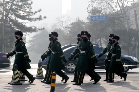 "Chinese paramilitary policemen wearing masks for protection against pollution march as the capital city is shrouded by smog in Beijing, Monday, Dec. 19, 2016. Chinese cities are limiting the number of cars on roads and have temporarily shut down factories to cut down pollution during a national ""red alert"" for smog. (AP Photo/Andy Wong)"