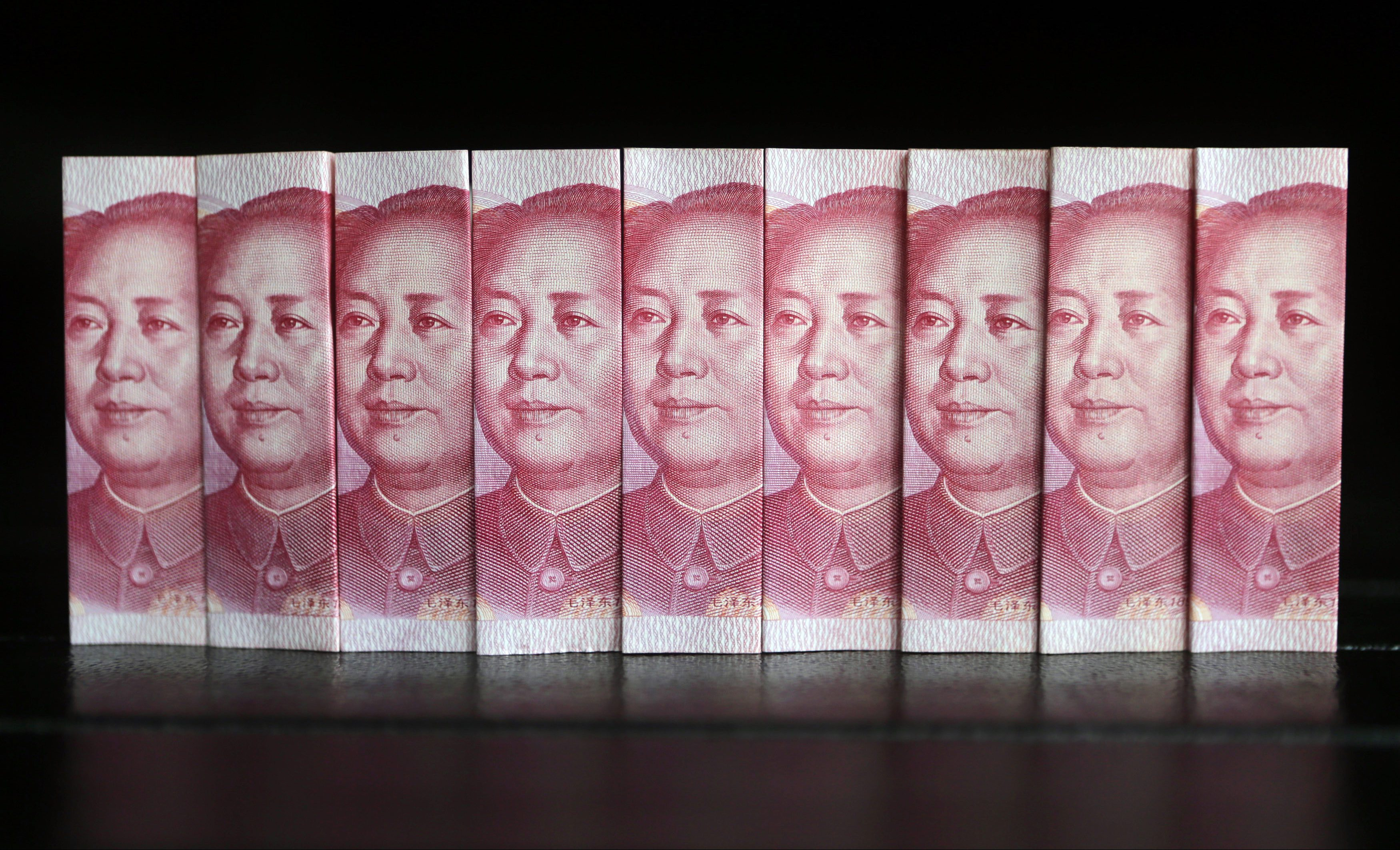 Chinese 100 yuan banknotes are seen in this picture illustration taken in Beijing July 11, 2013. China's central bank has standardised rules on cross-border yuan transactions for domestic banks and companies, the latest step to boost the yuan's global influence.