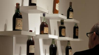 A man observes a shelf of high-end alcohol.