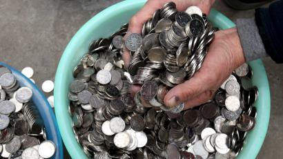 A person grabbing a handful coins from a bowl.