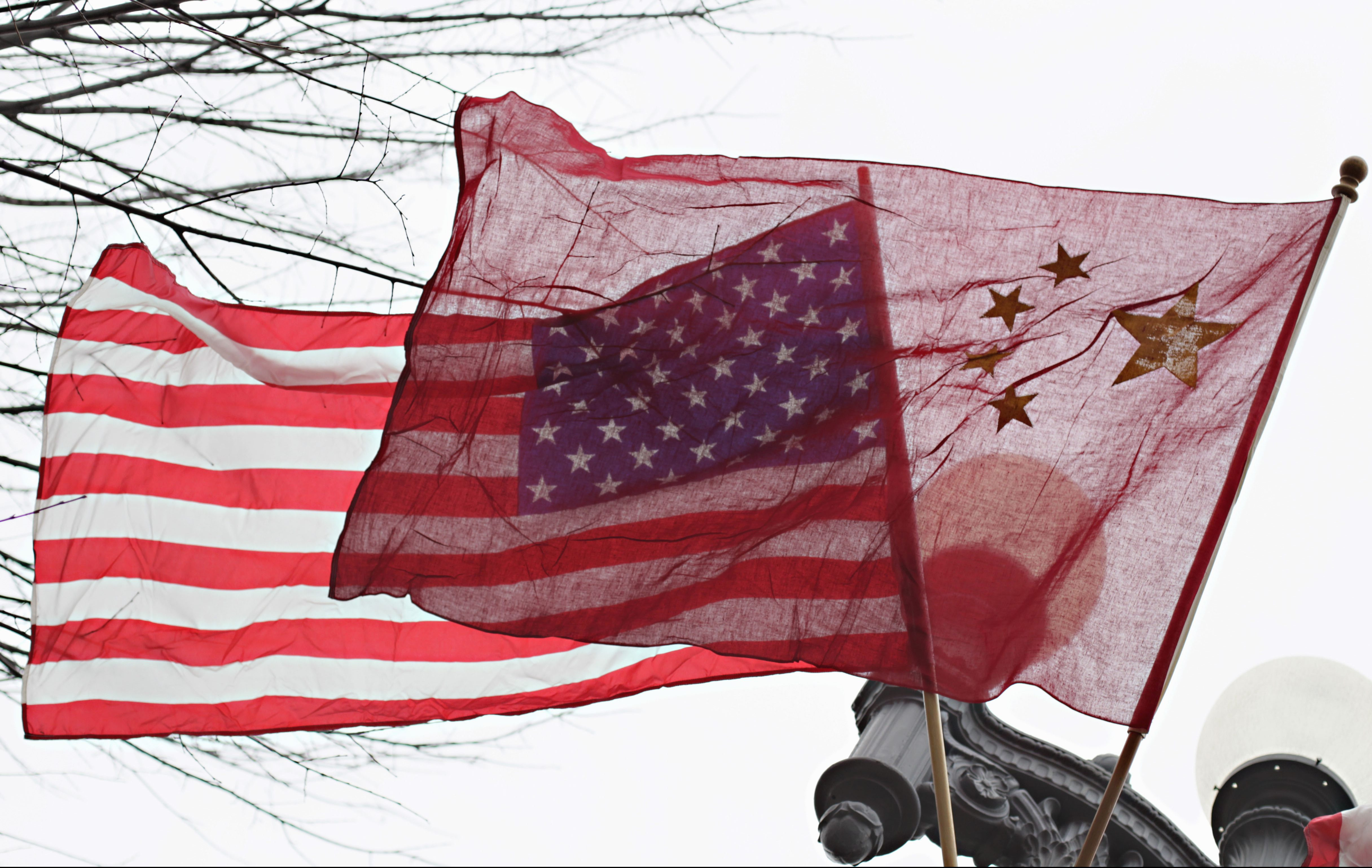 American and Chinese flags fly along Pennsylvania Avenue in front of the White House in Washington. The Justice Department's indictment last week of five Chinese military officials charged them with trying to pilfer confidential information from American companies. But even some of the alleged U.S. corporate victims of the hackers have little incentive to cheer any trade rupture with China. (AP Photo/Carolyn Kaster, File)