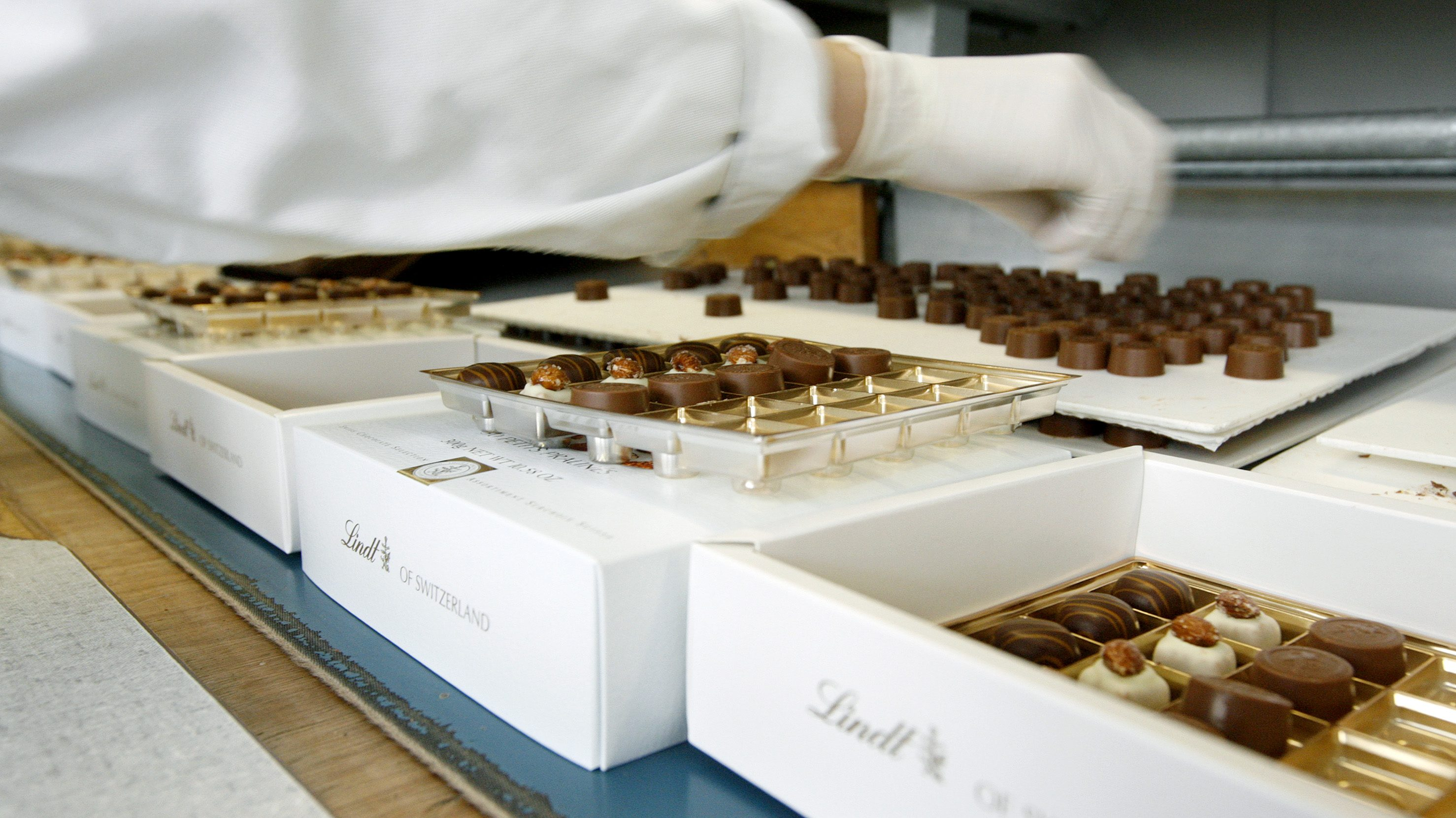Employee put pralines in boxes at the plant of Swiss chocolate producer Lindt & Spruengli AG in Kilchberg near Zurich in this April 10, 2008 file photo. The maker of Lindor pralines and gold-wrapped Easter bunnies posted a forecast-beating 5 percent rise in first-half net profit to 23 million Swiss francs ($20.95 million), boosted by upbeat demand for its Excellence and Creation 70% products. Picture taken April 10, 2008 REUTERS/Arnd Wiegmann/files (SWITZERLAND) - RTR21PJZ