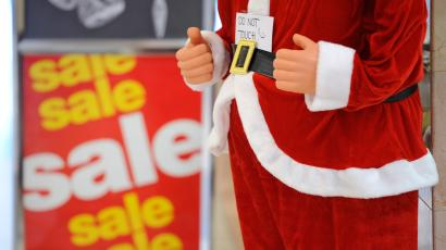 A Santa Claus in front of a Christmas sale sign
