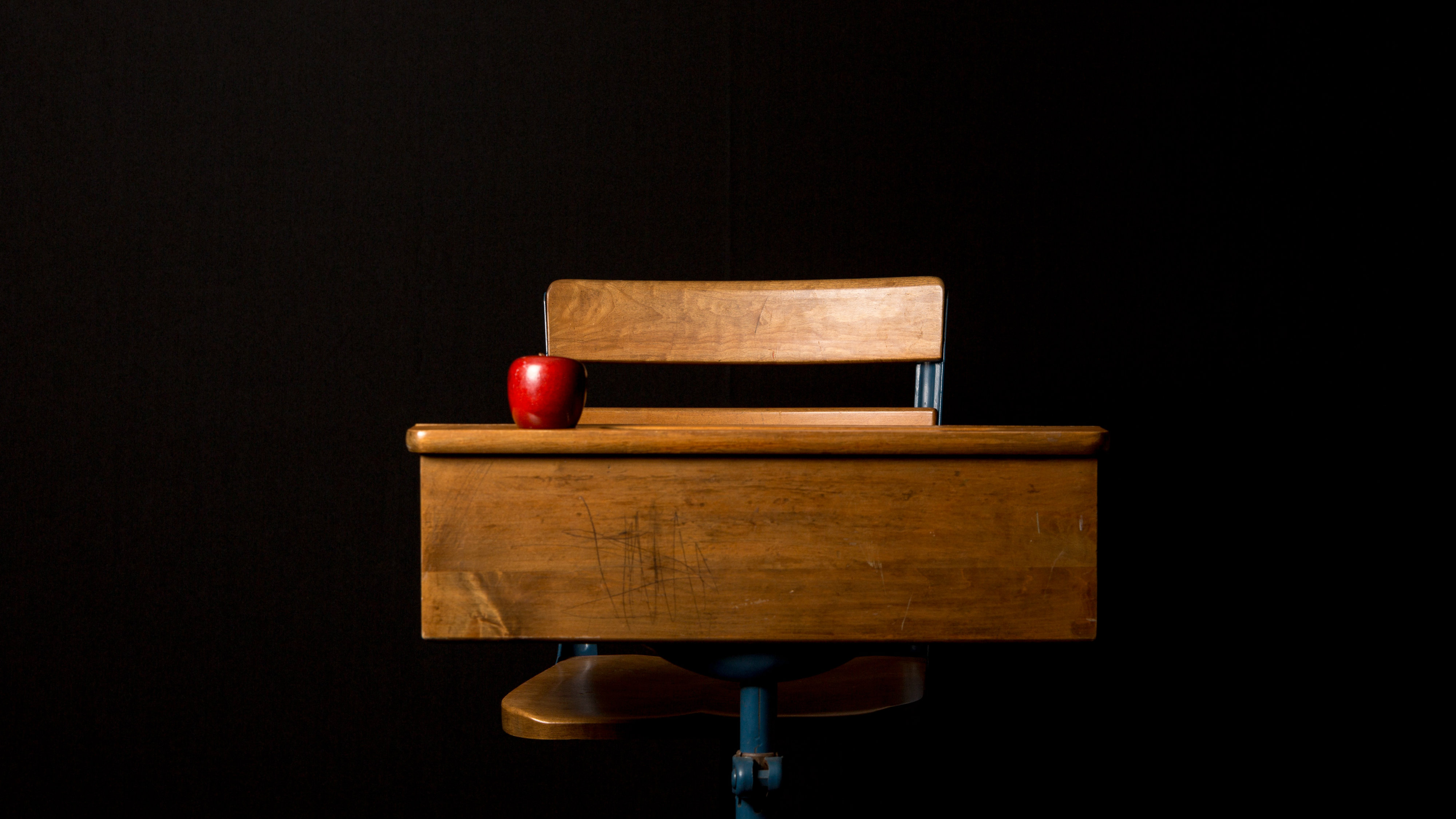 A classroom desk with black background