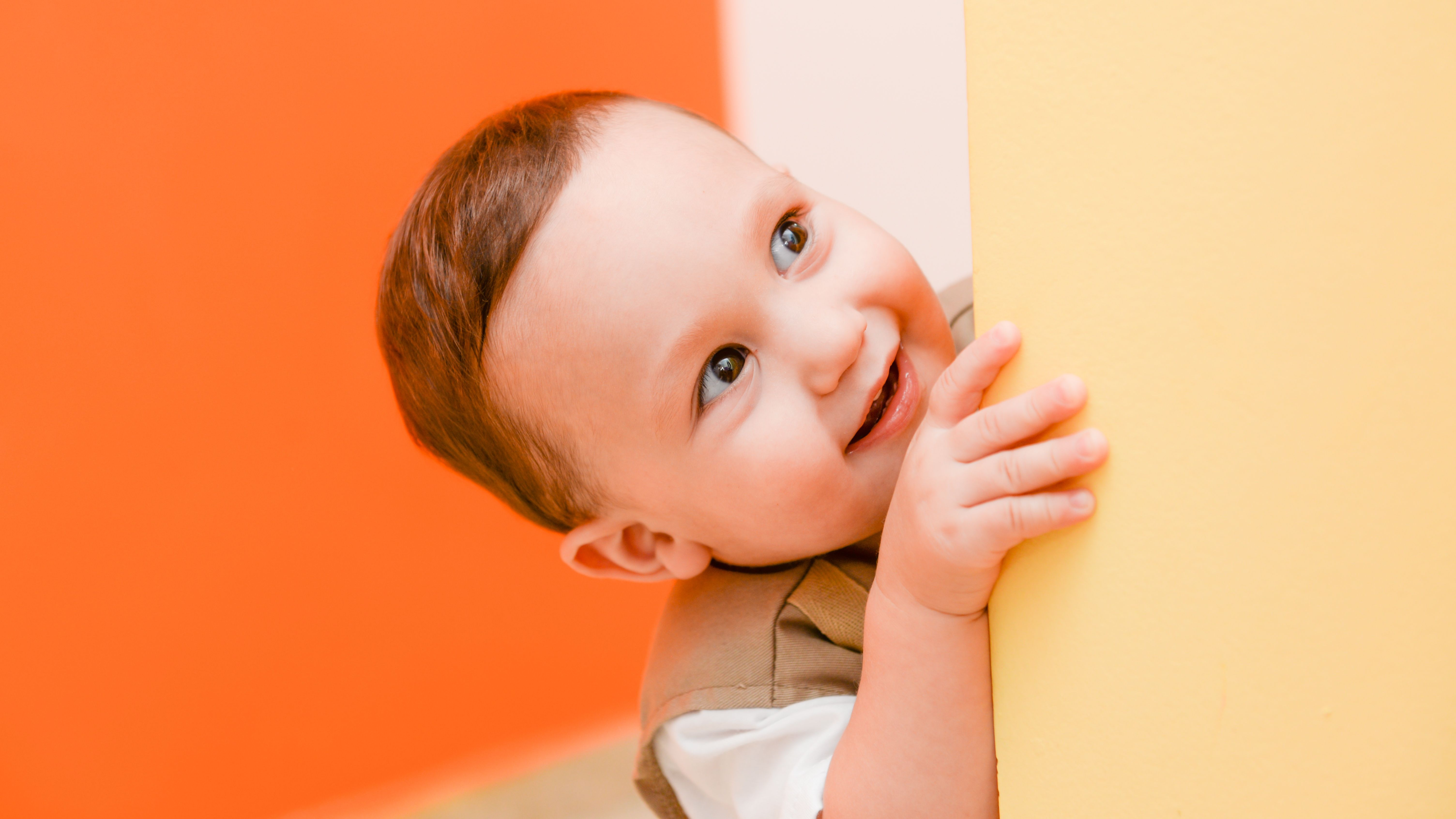 toddler boy peeks around corner in front of orange wall