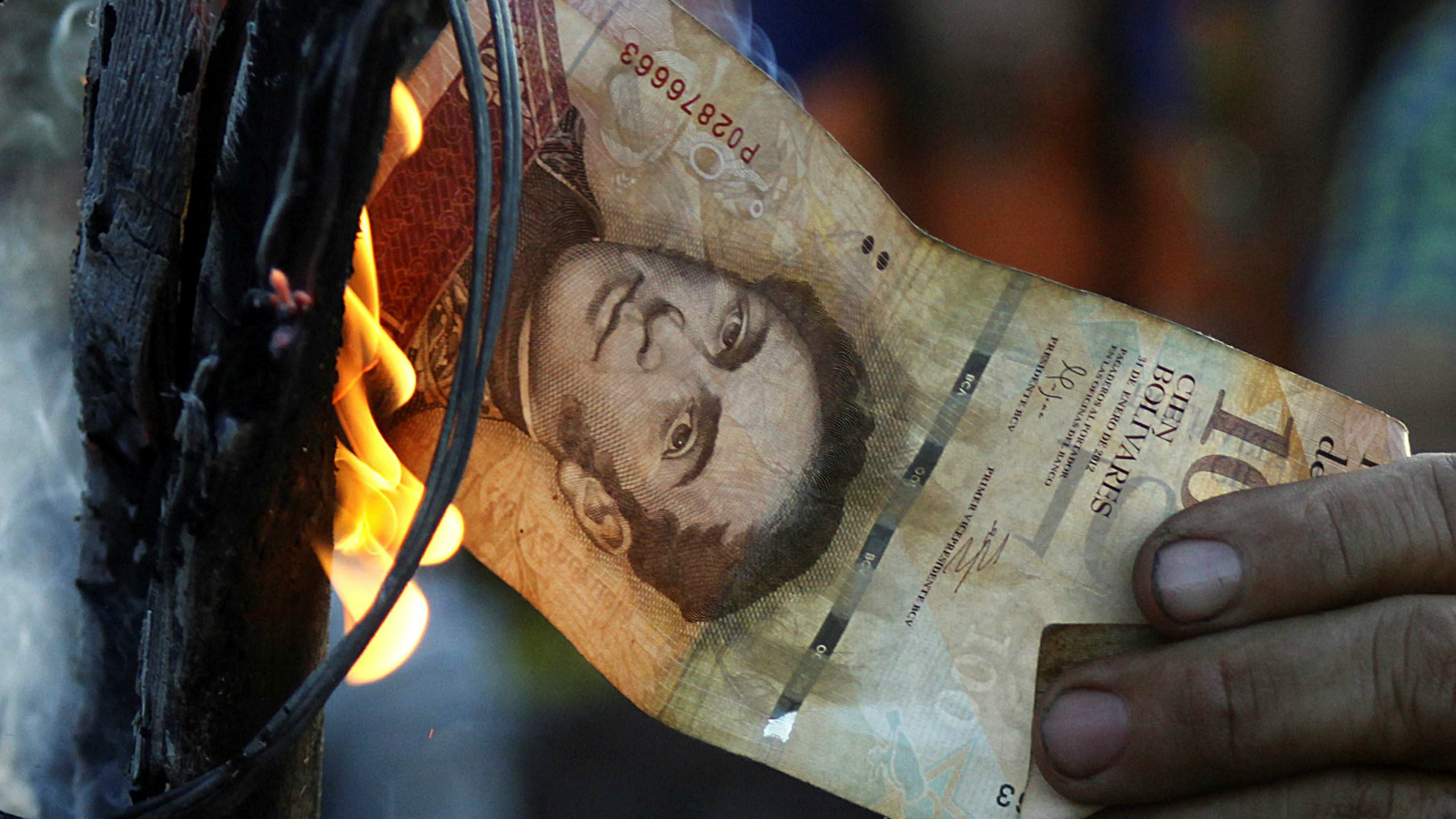 A man burns a 100-bolivar bill during a protest in El Pinal, Venezuela December 16, 2016.