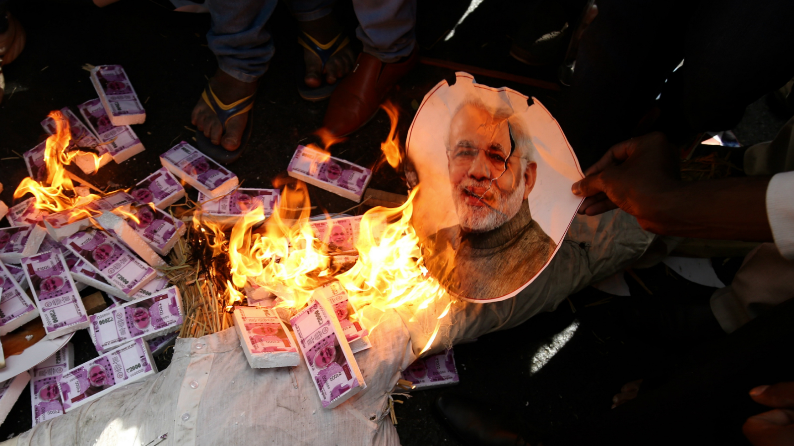 Protesters burn Indian Prime Minister Narendra Modi portrait during an opposition parties, including the Congress party workers, rally in support of 'Jan Aakrosh Diwas' and against the denomination, in Bangalore, India, 28 November 2016. Opposition parties, including the Congress, Left parties, Samajwadi Party and the Trinamool Congress, are observing 'Jan Aakrosh Diwas' on Monday to protest against the Centre's denomination move. Indian Prime Minister Narendra Modi announced the elimination of the 500 and 1,000 rupee bills at midnight on 08 November, for the purpose of fighting against 'black money' and corruption in the country. The decision sparked protests, while storekeepers complained about dwindling sales because many citizens lack the cash to buy the most basic products, as queues get longer at ATMs and banks.