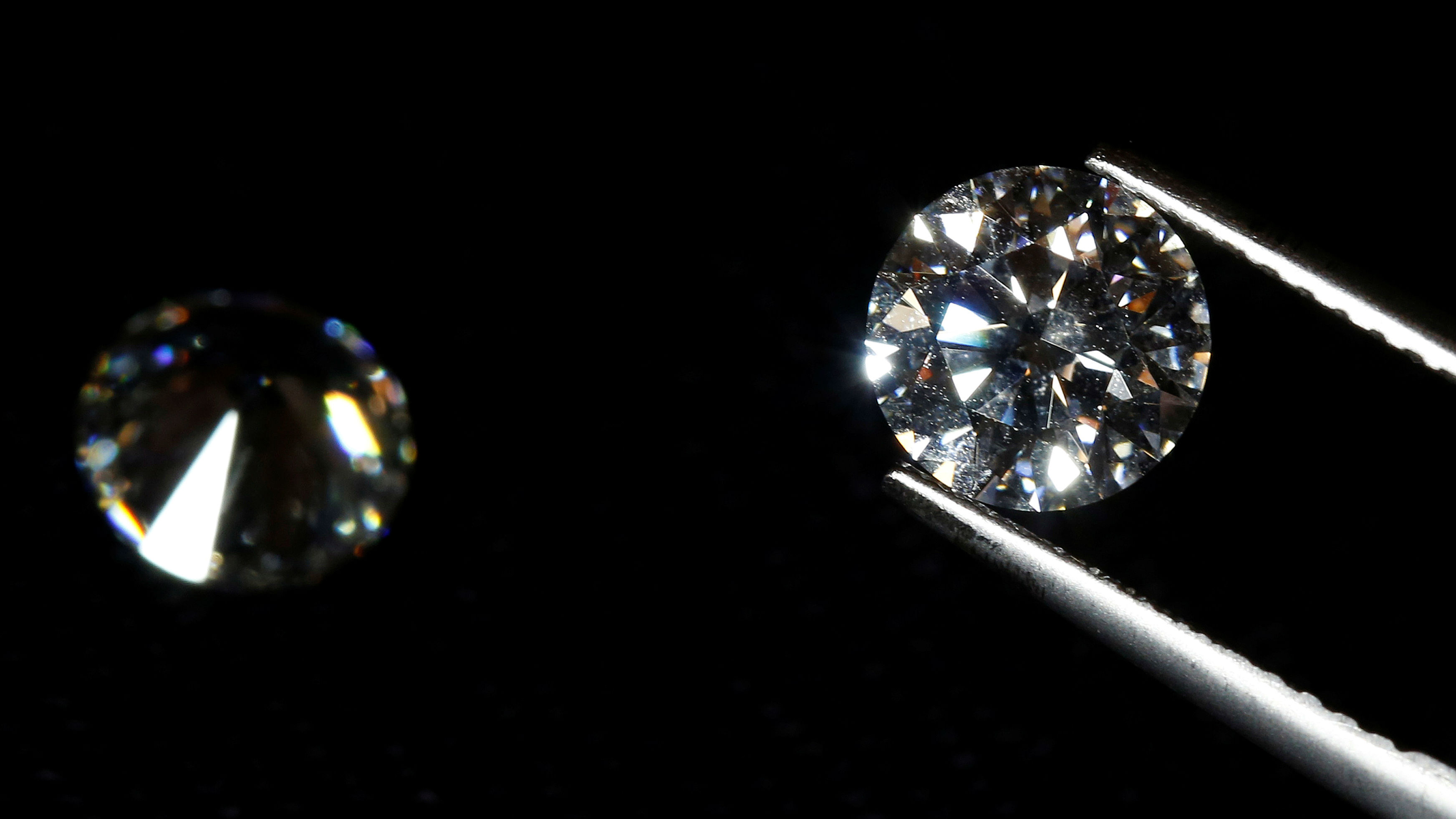 A close up of a diamond in gem-holding tools.