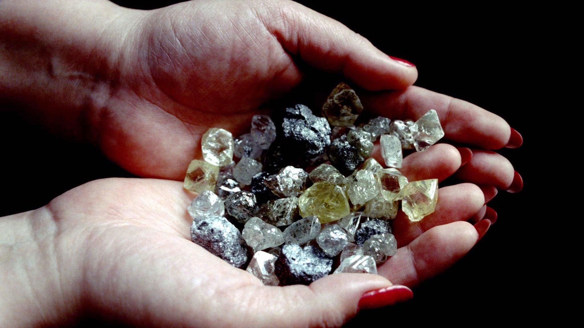 """A worker holds a handful of uncut diamonds found in the giant sand-pit called """"Udachny"""" (Lucky) in Siberia, March 6, where around 90 percent of Russian diamonds are found. A new agreement is expected to be signed soon between the Russian Federation and the South-African diamond corporation De Beers on the annual sale of Russian uncut diamonds, according to reports. - RTXHMX3"""