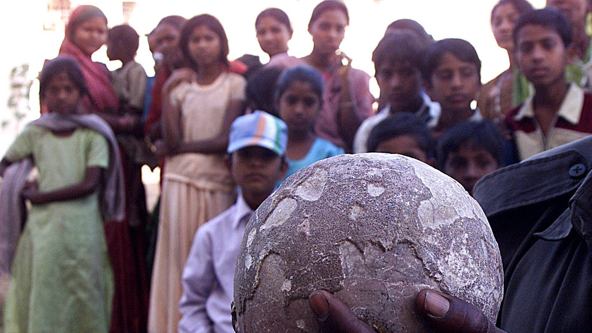 A government employee holds what he claims is a dinosaur's egg in the town of Balasinore in Gujarat state, India on 24 February 2004. The egg weighs about five kilograms and is believed to be at least 65 million years old. Such 'eggs' are commonly found in Balasinore. Last August a team of scientists from India and the United States found dinosaur fossils around the same area, and named it Rajasaurus Narmadenis which means the princely reptile from the Narmada river.
