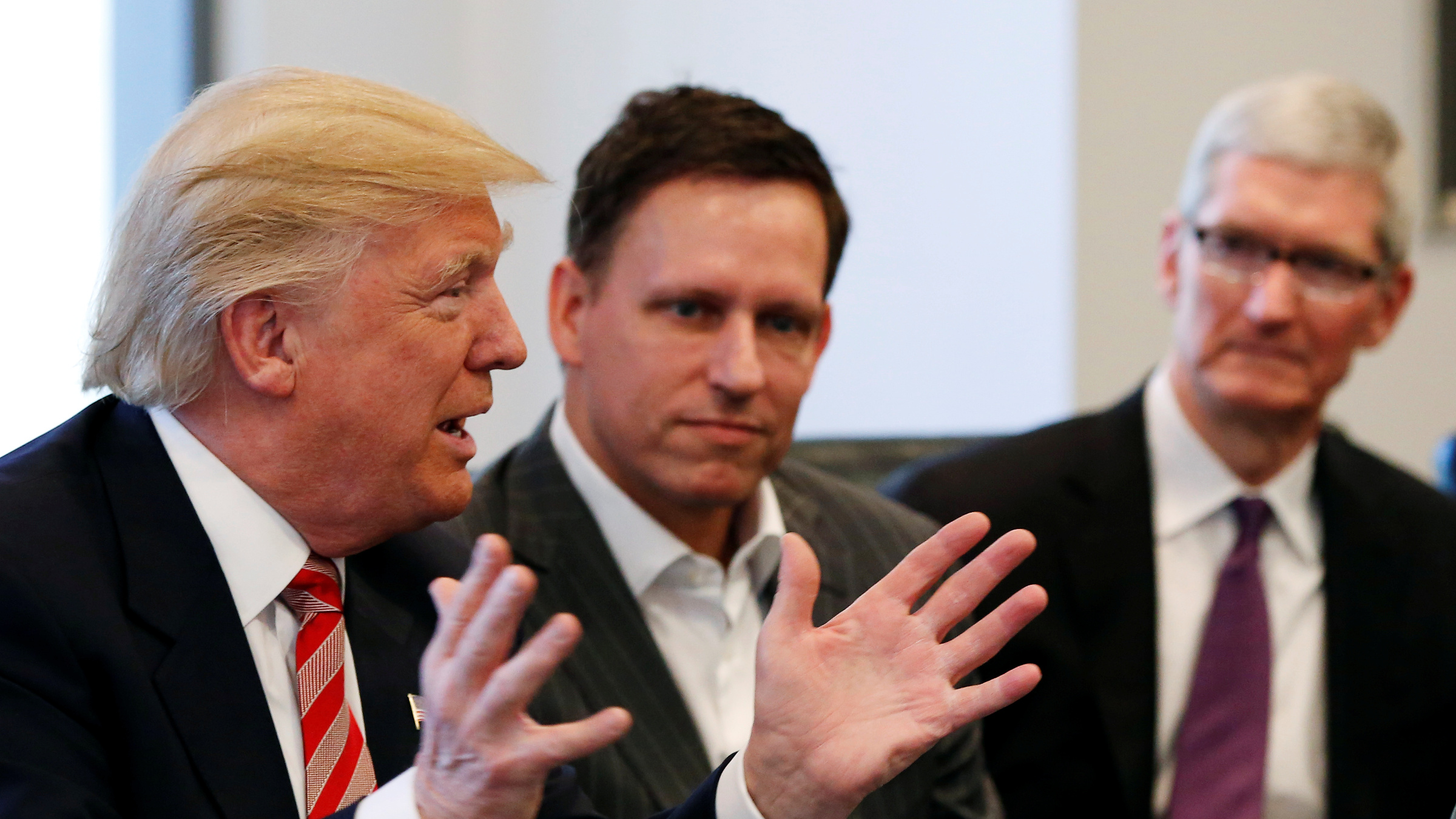 U.S. President-elect Donald Trump speaks as PayPal co-founder and Facebook board member Peter Thiel (C) and Apple Inc CEO Tim Cook look on during a meeting with technology leaders at Trump Tower in New York U.S., December 14, 2016.