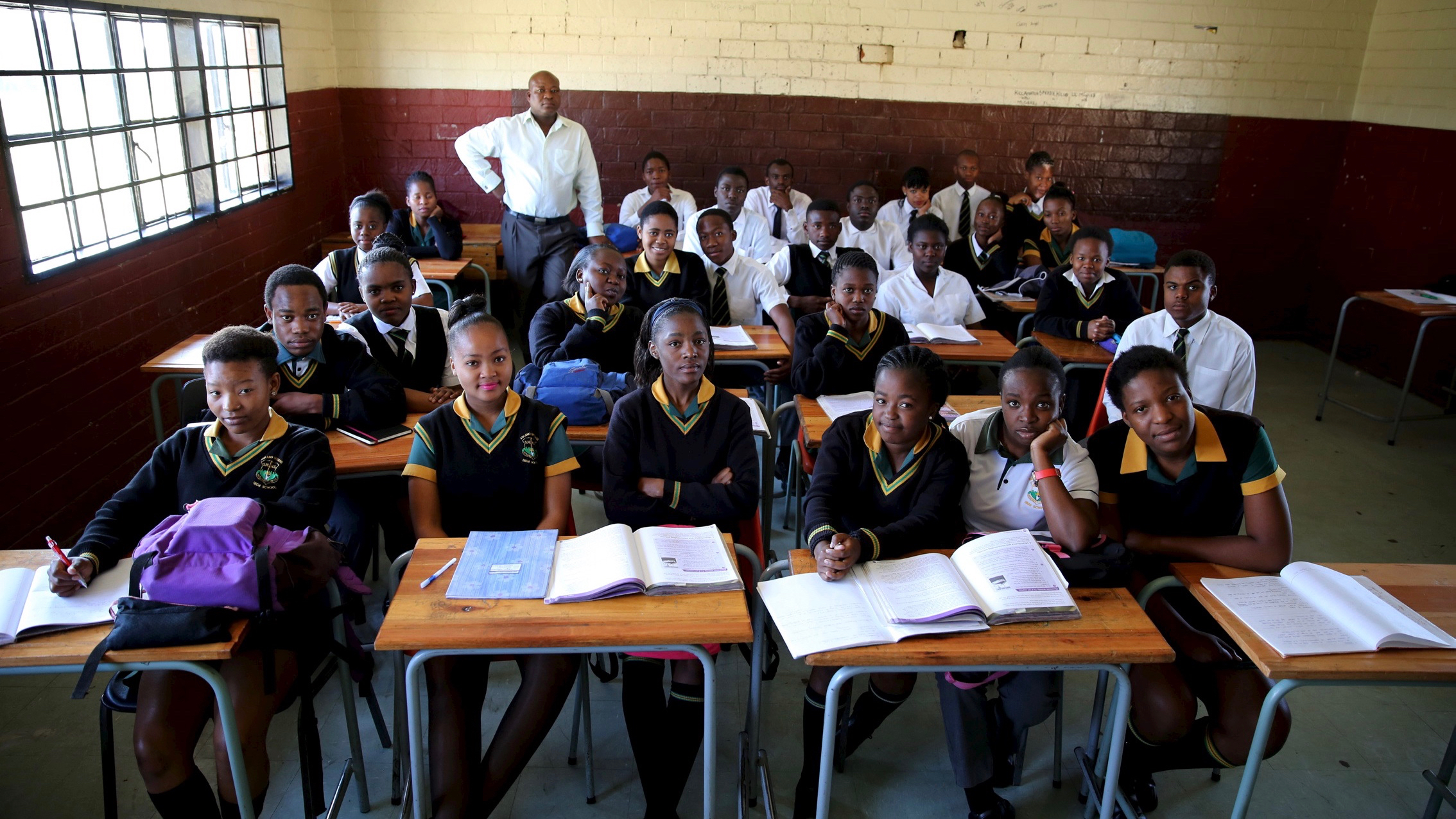 "Teacher Reginald Sikhwari poses for a picture with his class of grade 11 students at Sekano-Ntoane school in Soweto, South Africa, September 17, 2015. Nearly three years after Taliban gunmen shot Pakistani schoolgirl Malala Yousafzai, the teenage activist last week urged world leaders gathered in New York to help millions more children go to school. World Teachers' Day falls on 5 October, a Unesco initiative highlighting the work of educators struggling to teach children amid intimidation in Pakistan, conflict in Syria or poverty in Vietnam. Even so, there have been some improvements: the number of children not attending primary school has plummeted to an estimated 57 million worldwide in 2015, the U.N. says, down from 100 million 15 years ago. Reuters photographers have documented learning around the world, from well-resourced schools to pupils crammed into corridors in the Philippines, on boats in Brazil or in crowded classrooms in Burundi. REUTERS/Siphiwe Sibeko PICTURE 39 OF 47 FOR WIDER IMAGE STORY ""SCHOOLS AROUND THE WORLD""SEARCH ""EDUCATORS SCHOOLS"" FOR ALL IMAGES - RTS2DWQ"