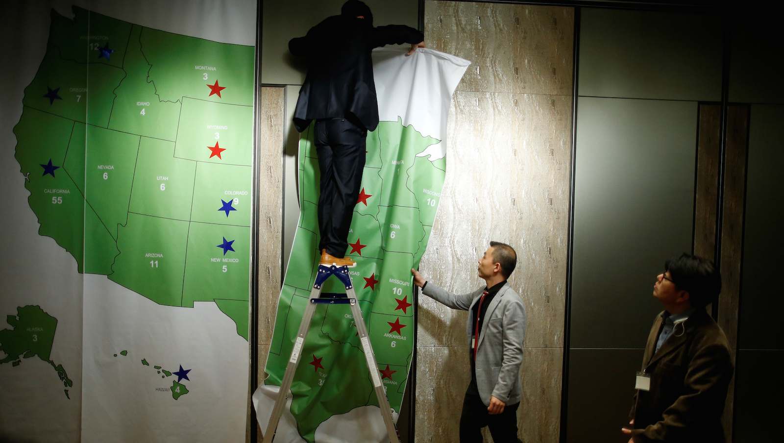 A man removes the Electoral College Map after a U.S. Election Watch event hosted by the U.S. Embassy at a hotel in Seoul, South Korea, November 9, 2016. REUTERS/Kim Hong-Ji - RTX2SOUR
