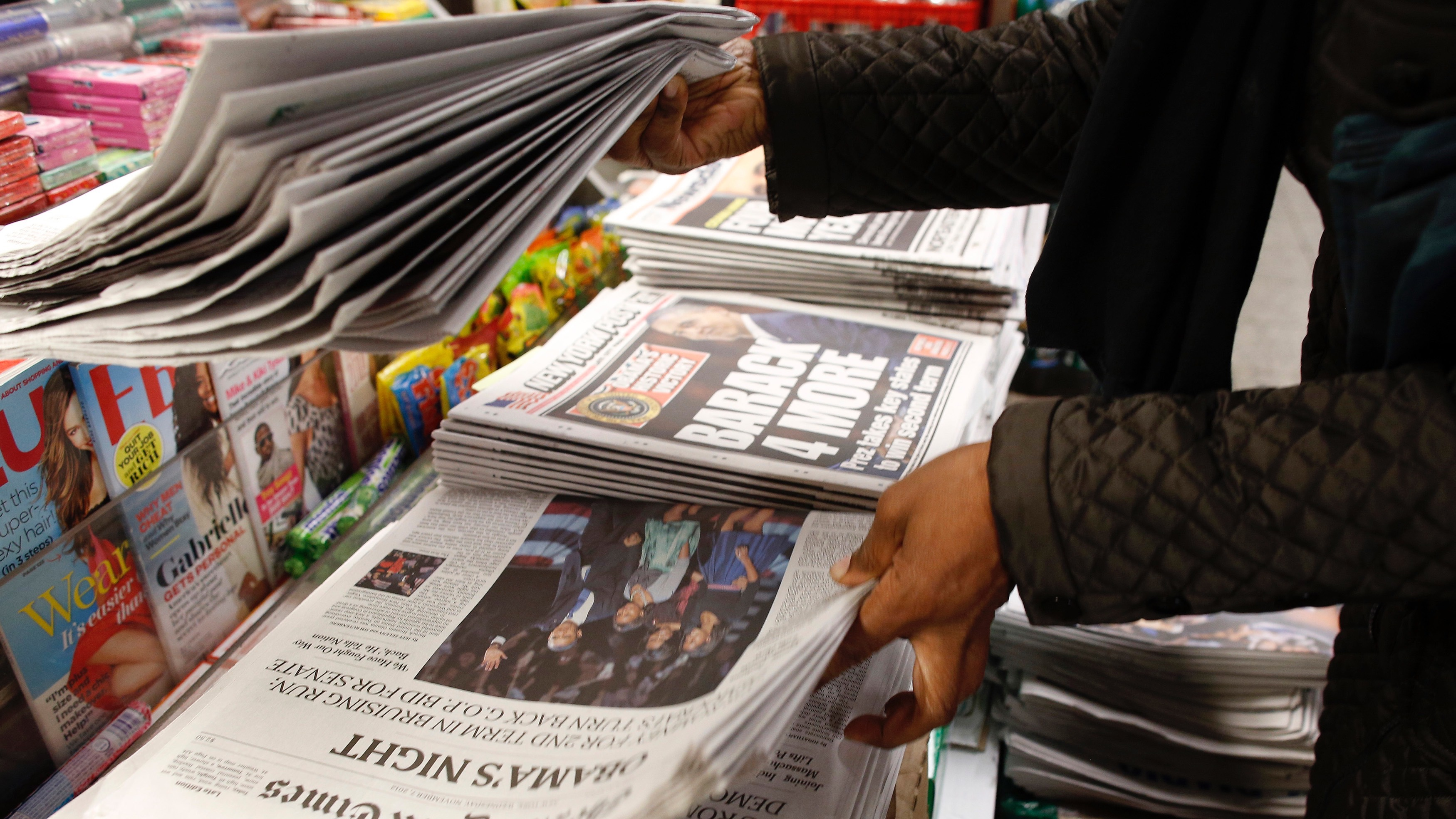 People purchase newspapers showing Barack Obama winning the U.S. presidential election on their frontpages, at a news stand in Times Square, New York November 7, 2012.  Growing optimism about the economy and a big turnout of the core Democratic coalition sealed President Barack Obama's re-election victory over Republican challenger Mitt Romney on Wednesday. REUTERS/Chip East (UNITED STATES - Tags: POLITICS USA PRESIDENTIAL ELECTION ELECTIONS MEDIA) - RTR3A4M3