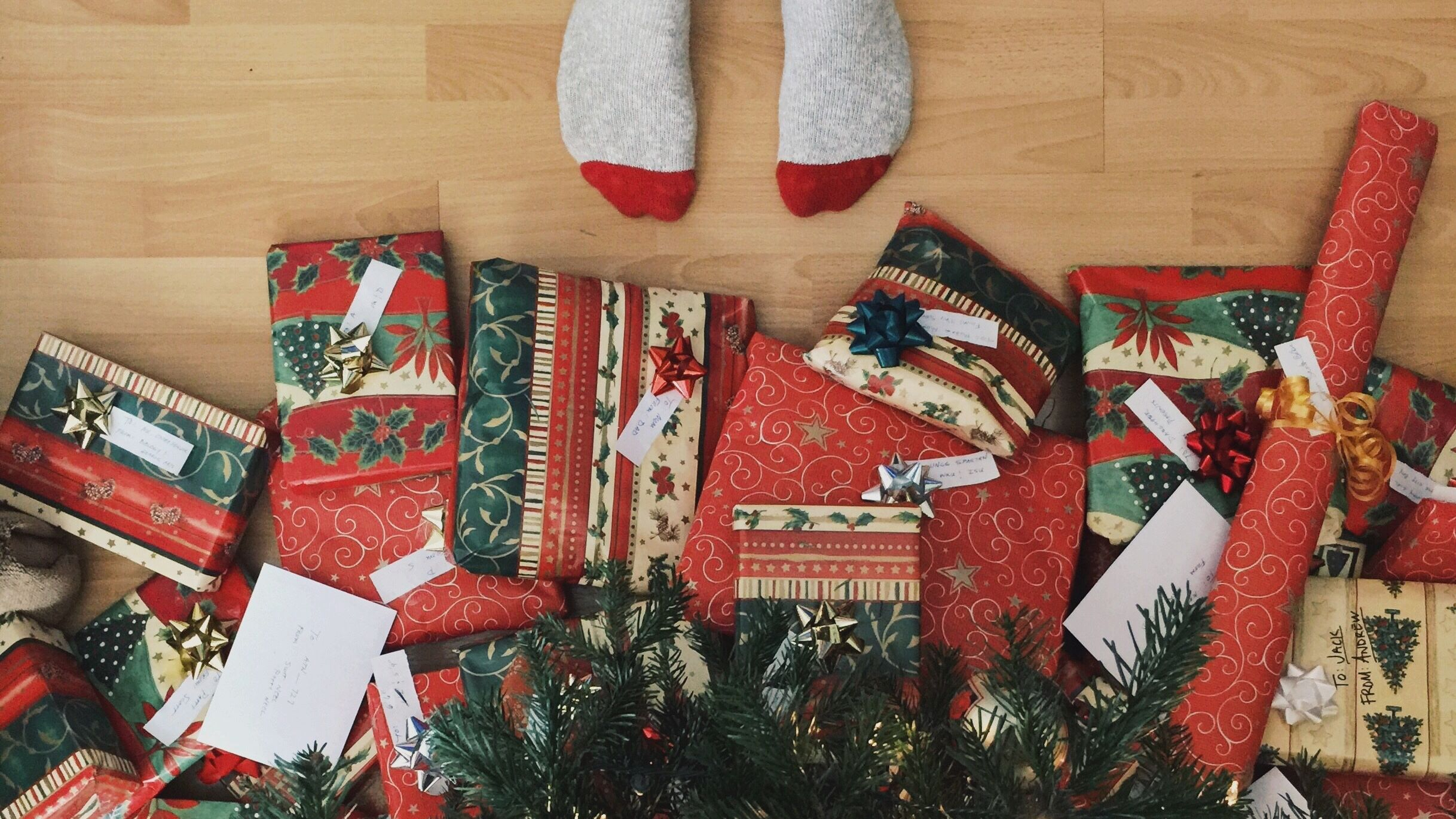 feets in socks underneath christmas tree with many wrapped presents