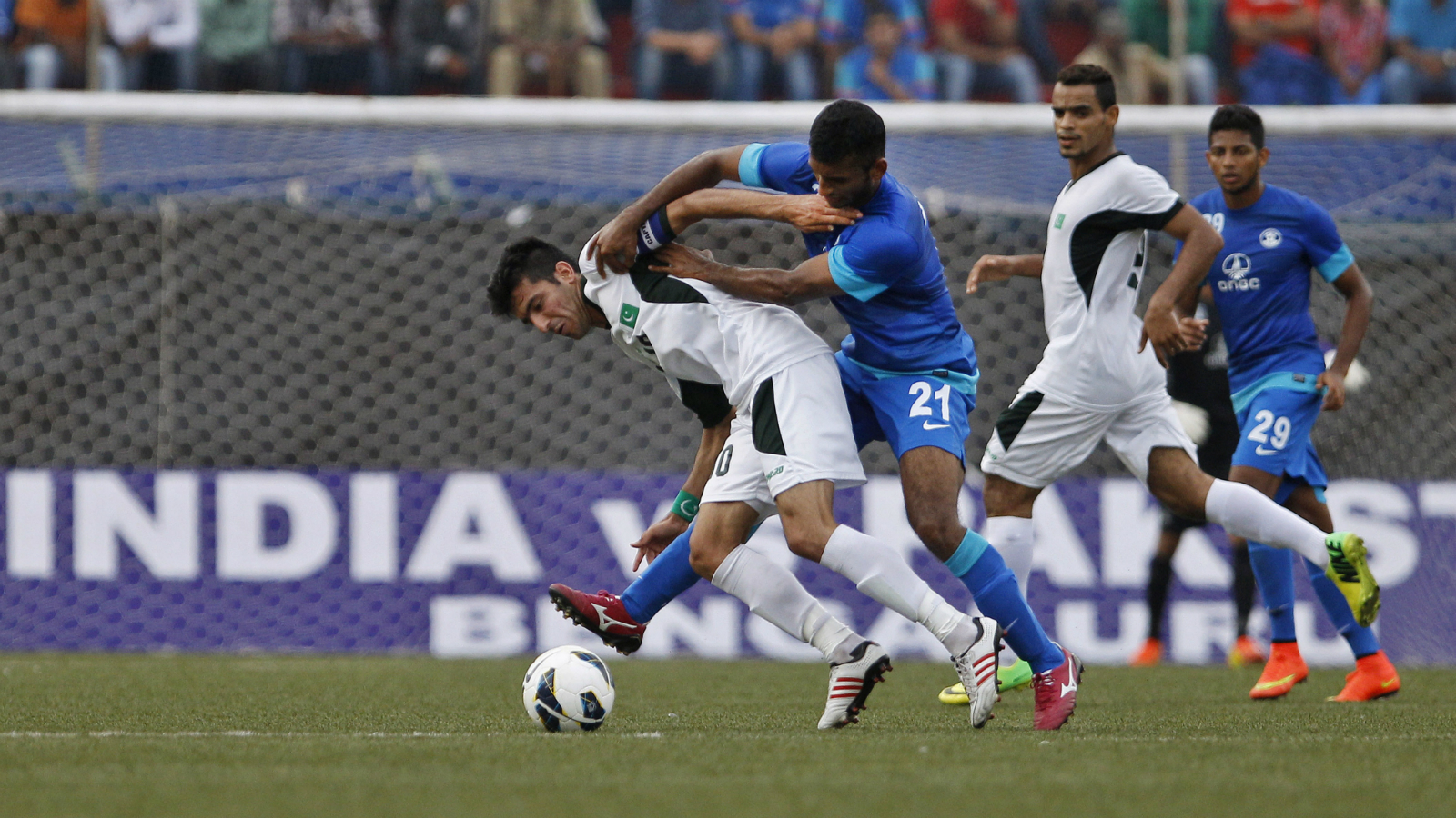 Pakistan team captain Kaleem Ullah, left, and India's Pronoy Halder (21) jostle to get control of the ball during the first match of the two-match friendly soccer tournament between Indian and Pakistan in Bangalore, India, Sunday, Aug. 17, 2014. India won the match 1-0.