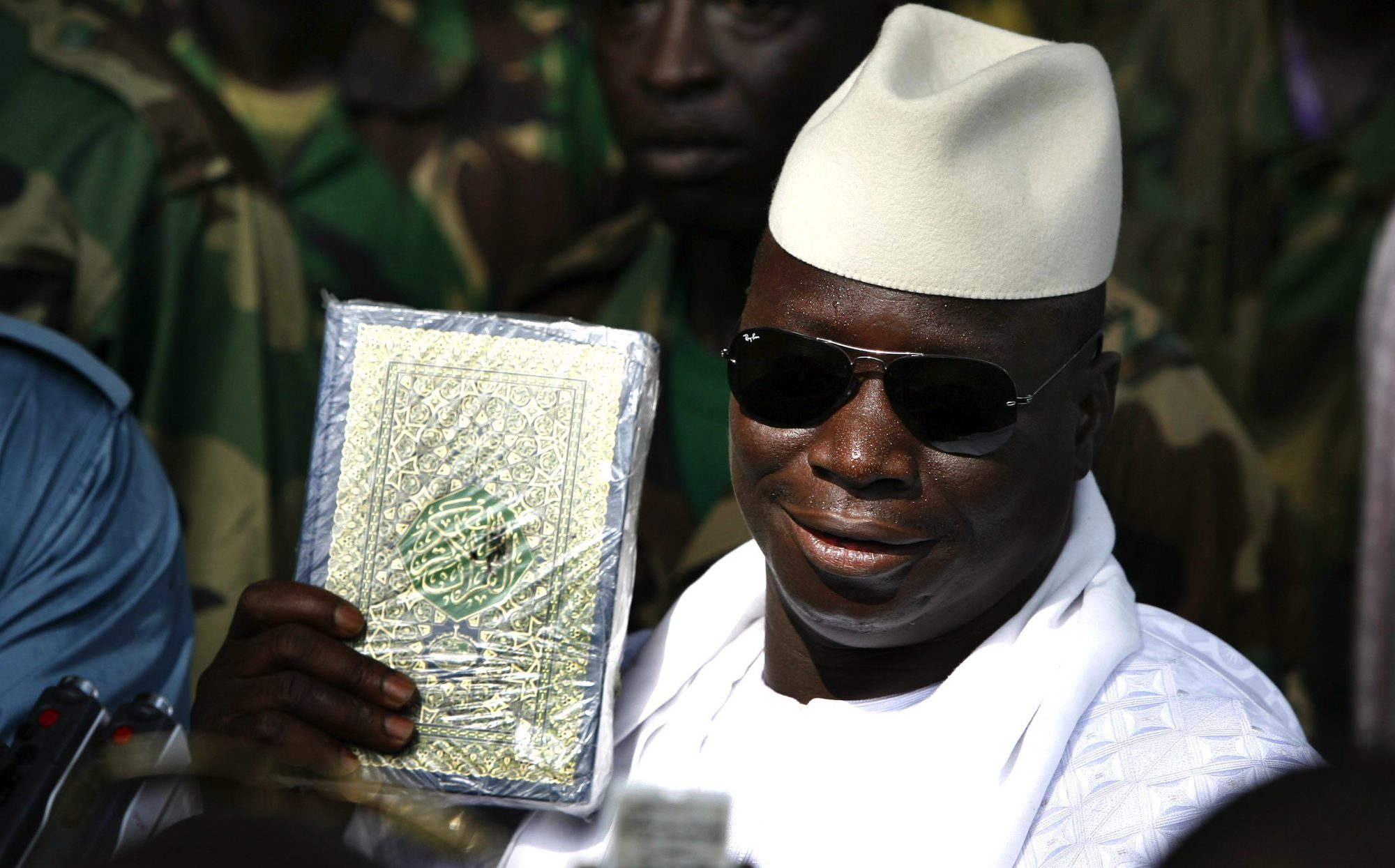 Gambian President Yahya Jammeh holds up a Koran while speaking to the media after casting his ballot in the presidential elections in Banjul September 22, 2006. Voters in the tiny West African nation of Gambia went to the polls on Friday in a presidential election widely expected to extend the iron-fisted rule of incumbent Jammeh for a third elected term.