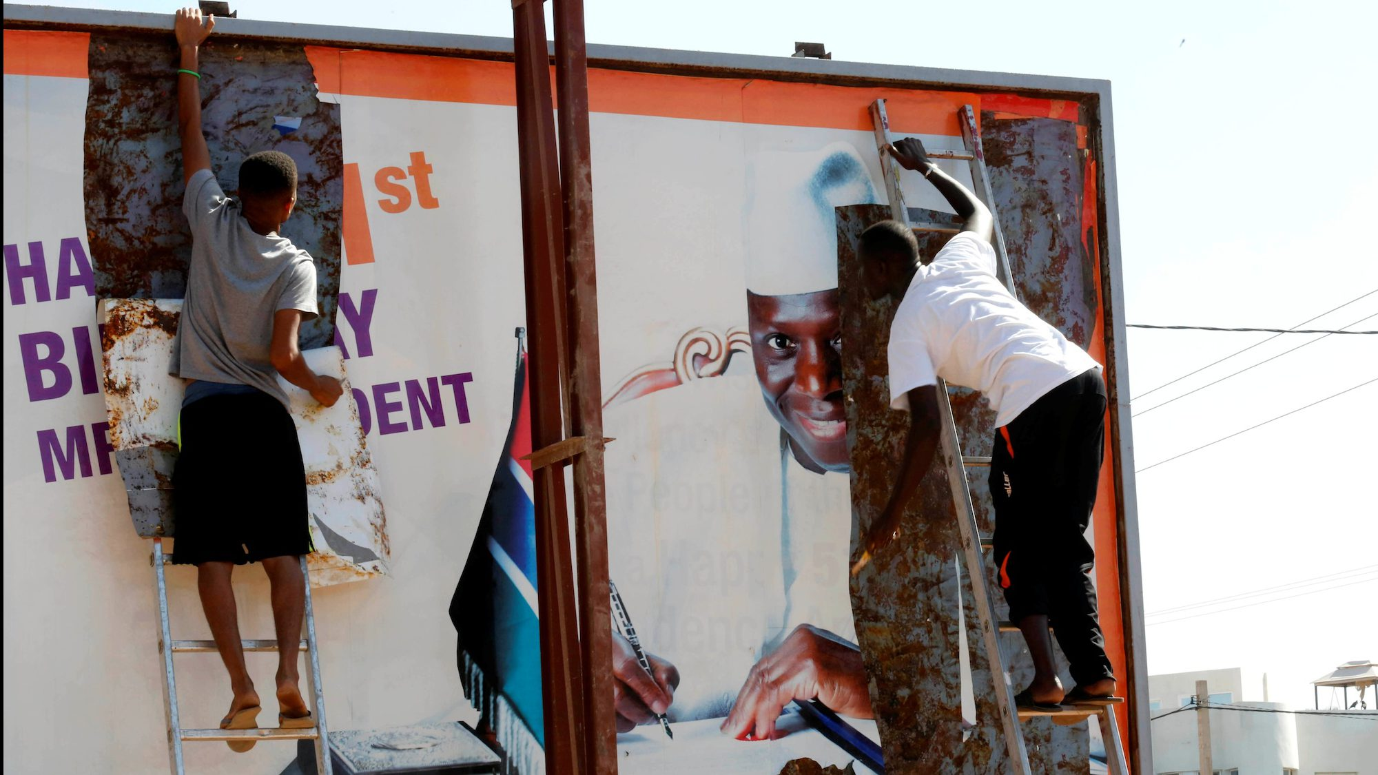 Posters of Gambian president Yaya Jammeh come down.