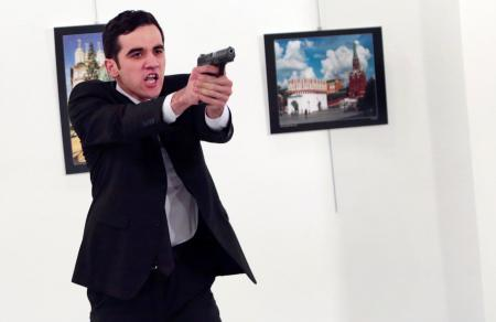 "ADDS THE NAME OF THE GUNMAN - The attacker identified as Mevlut Mert Altintas holds up a gun after shooting Andrei Karlov, the Russian Ambassador to Turkey on Dec.19,2016. Shouting ""Don't forget Aleppo! Don't forget Syria!"" Altintas fatally shot Karlov in front of stunned onlookers at a photo exhibit. Police killed the assailant after a shootout. (AP Photo/Burhan Ozbilici)"