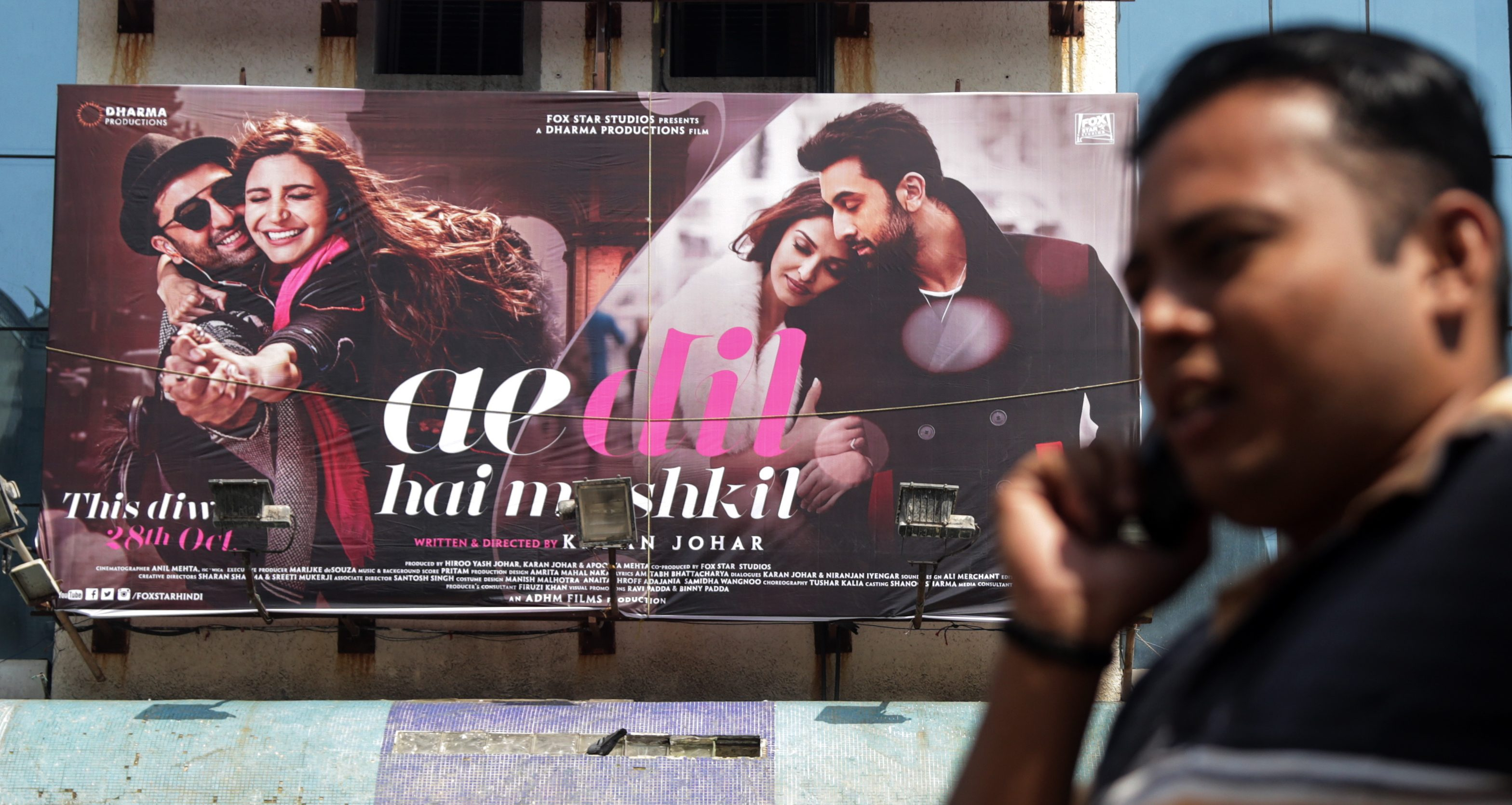 People walk past a theater screening the Bollywood movie 'Ae Dil Hai Mushkil' (This Heart is Complicated) on the first day of its release in Mumbai, India, 28 October 2016. According to reports, after the attack on an Indian army camp in Uri close to the Line of Control, which divides Kashmir between India and Pakistan, Raj Thackeray-led Maharashtra Navnirman Sena (MNS) threatened to stall the release of the movie 'Ae Dil Hai Mushkil,' starring Indian actors Ranbir Kapoor, Anushka Sharma, Aishwarya Rai Bachchan and Pakistani actor Fawad Khan, but after the intervention of the state government, MNS agreed to let the film release with the condition that they don't hire any Pakistani artists in future.