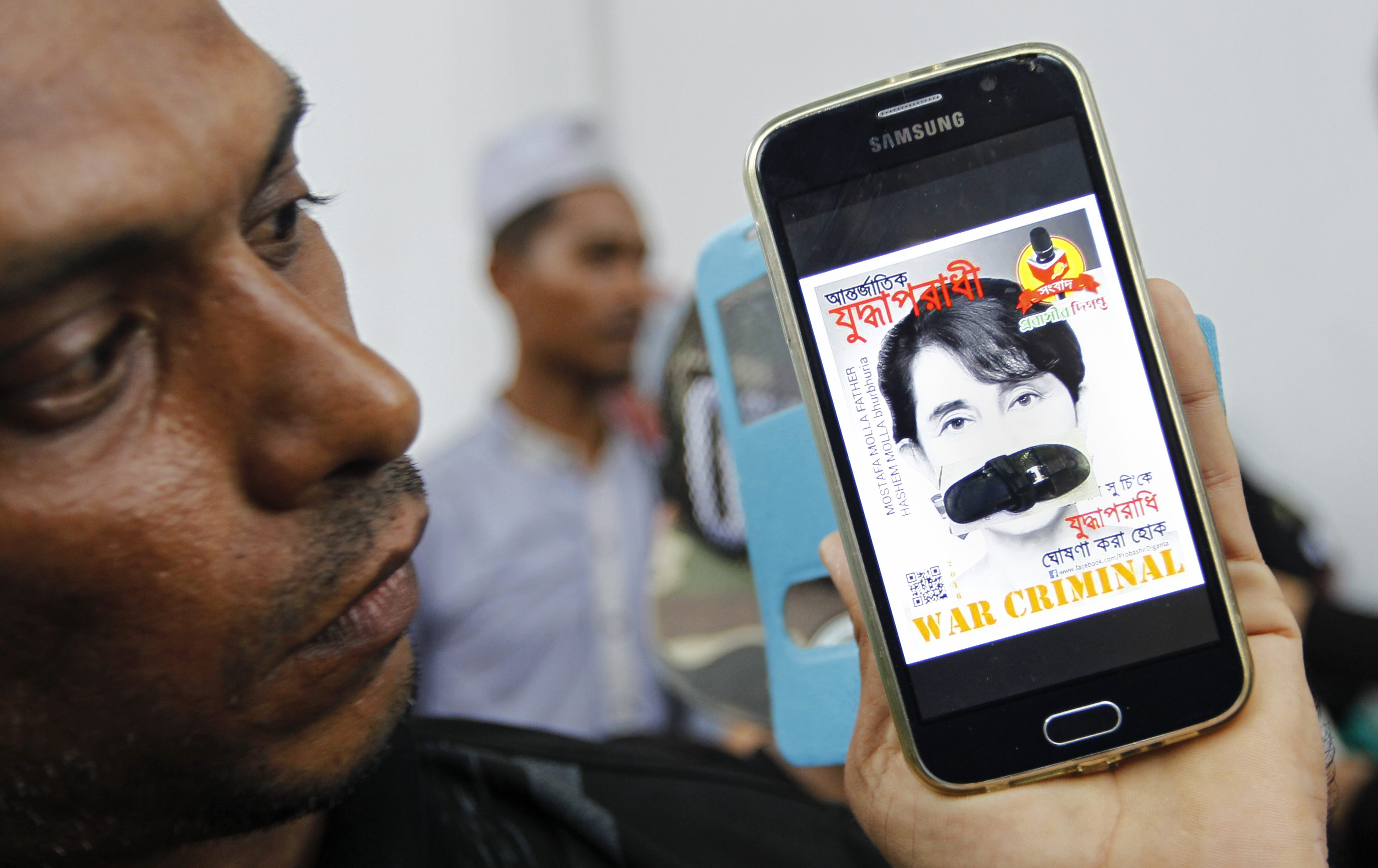 A Rohingya migrant shows a mobile phone displaying a photograph of Myanmar's State Counsellor and Foreign Minister Aung San Suu Kyi with her mouth covered with a flip flop and a banner reading 'War Criminal' during a protest against Myanmar's recent violence on Rohingya people, outside the Myanmar embassy in Bangkok, Thailand, 25 November 2016.