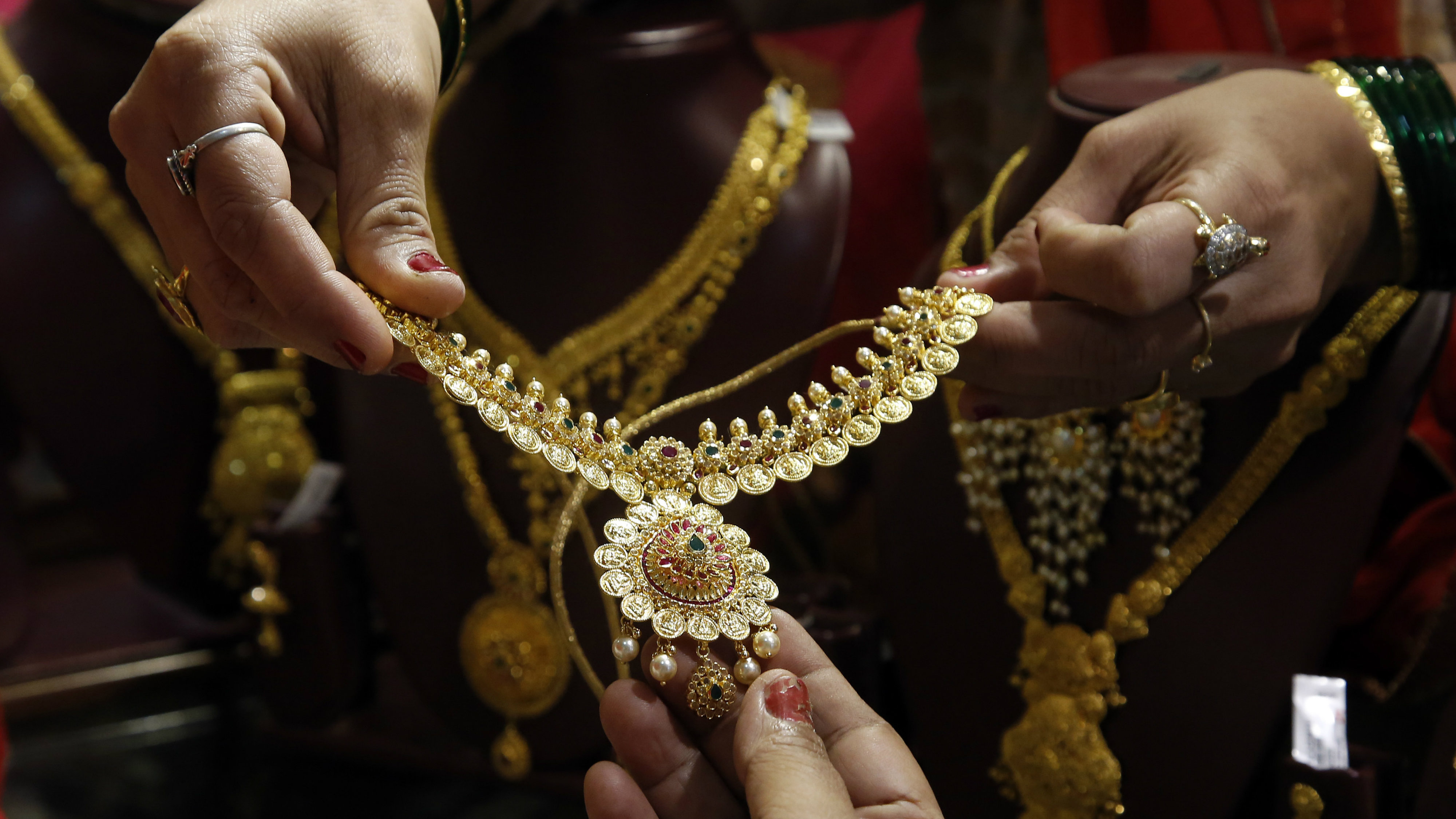 Indians look at a gold jewelry item as they shop on the occasion of 'Akshay Tritiya' in Mumbai, India, Monday, May 9, 2016. Monday marks the Hindu festival Akshay Tritiya, which is considered auspicious for buying gold among other things.