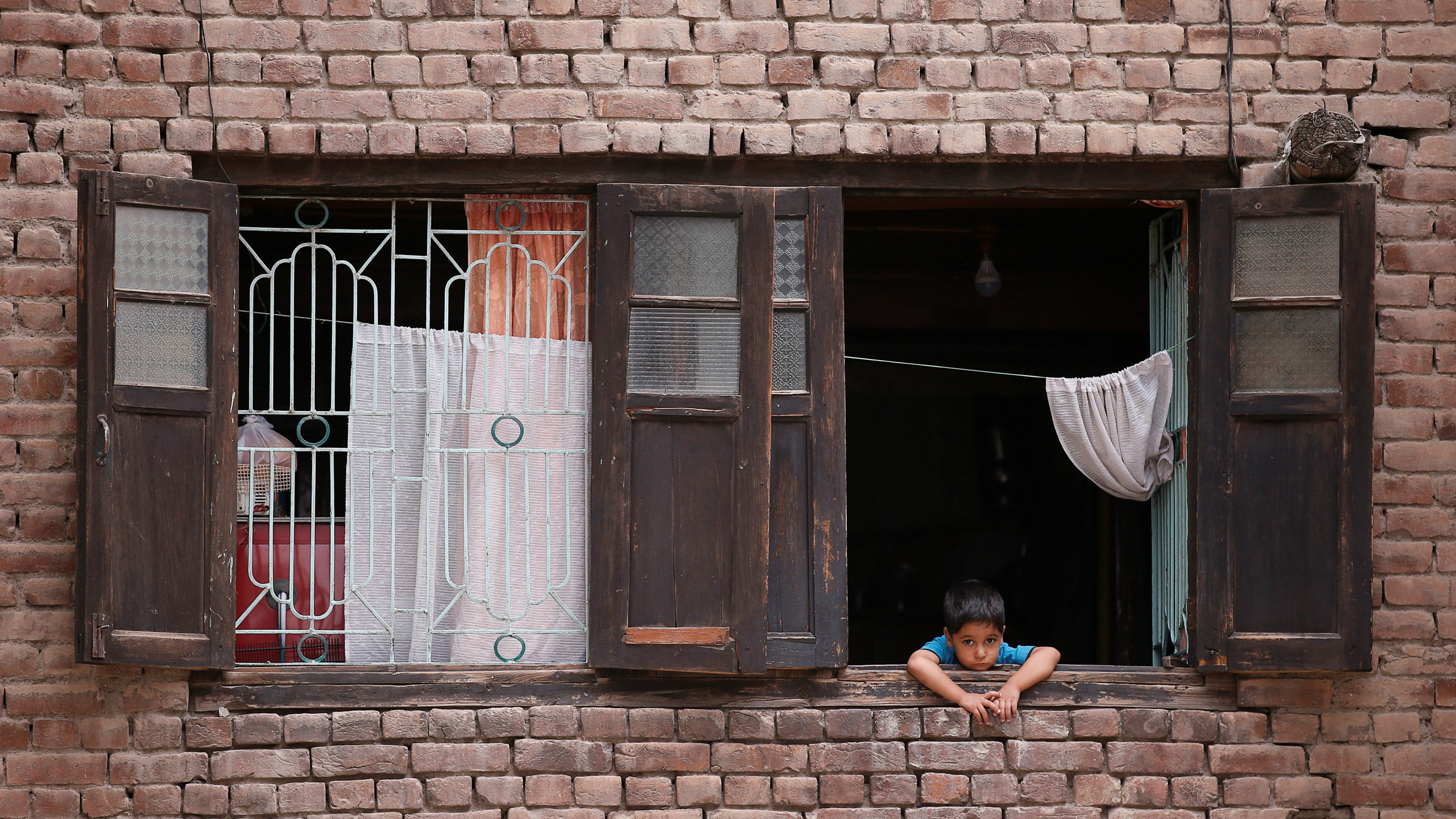 A boy looks out from a window of his house during a curfew in Srinagar, July 17, 2016.