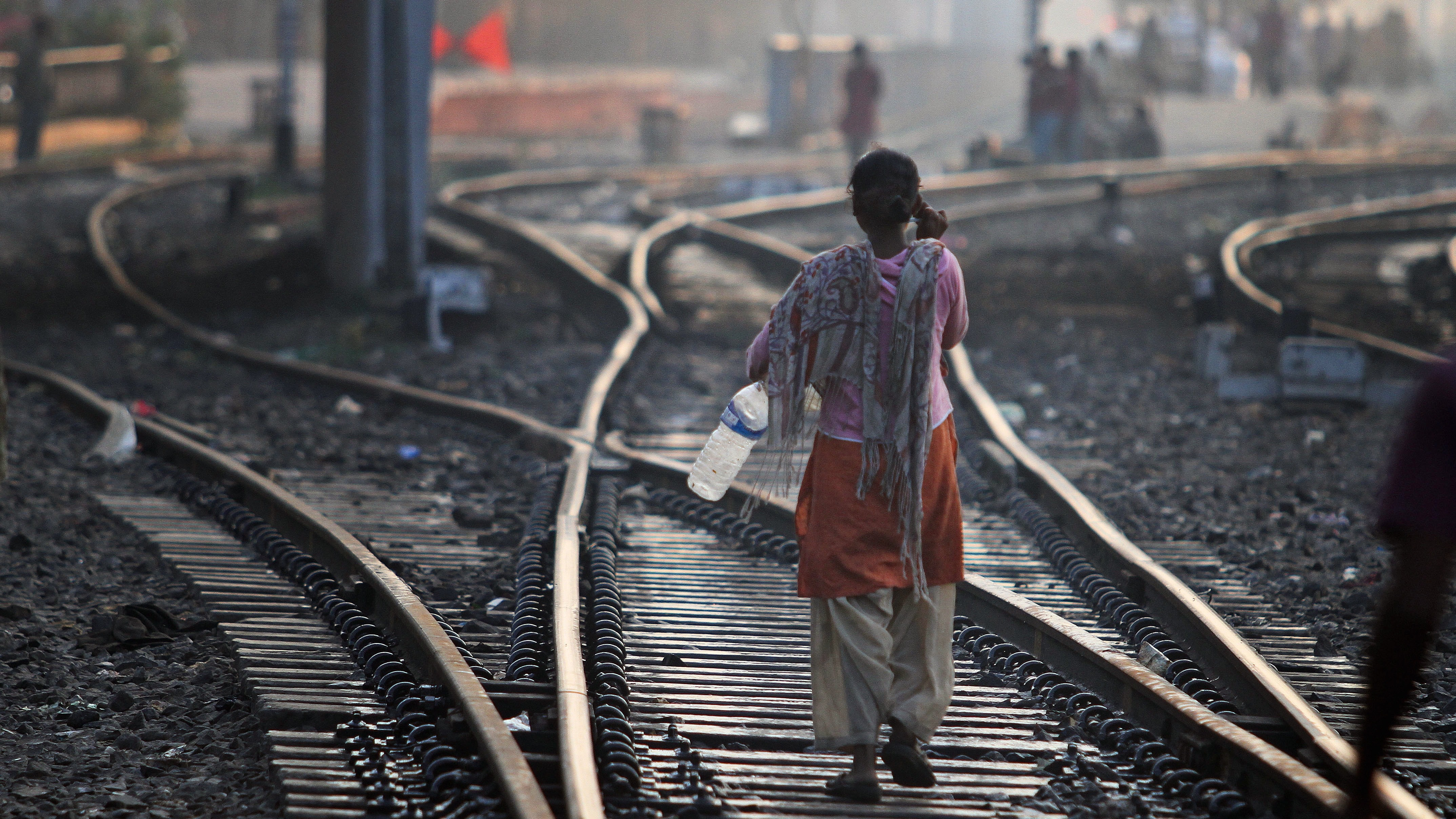 An Indian woman walks after defecating on a railway track, on World Toilet Day in Gauhati, India, Wednesday, Nov. 19 2014. India is considered to have the world's worst sanitation record despite spending some $3 billion since 1986 on sanitation programs, according to government figures. Building toilets in rural India, where hundreds of millions are still defecating outdoors, will not be enough to improve public health, according to a study published last month. (AP Photo/Anupam Nath)