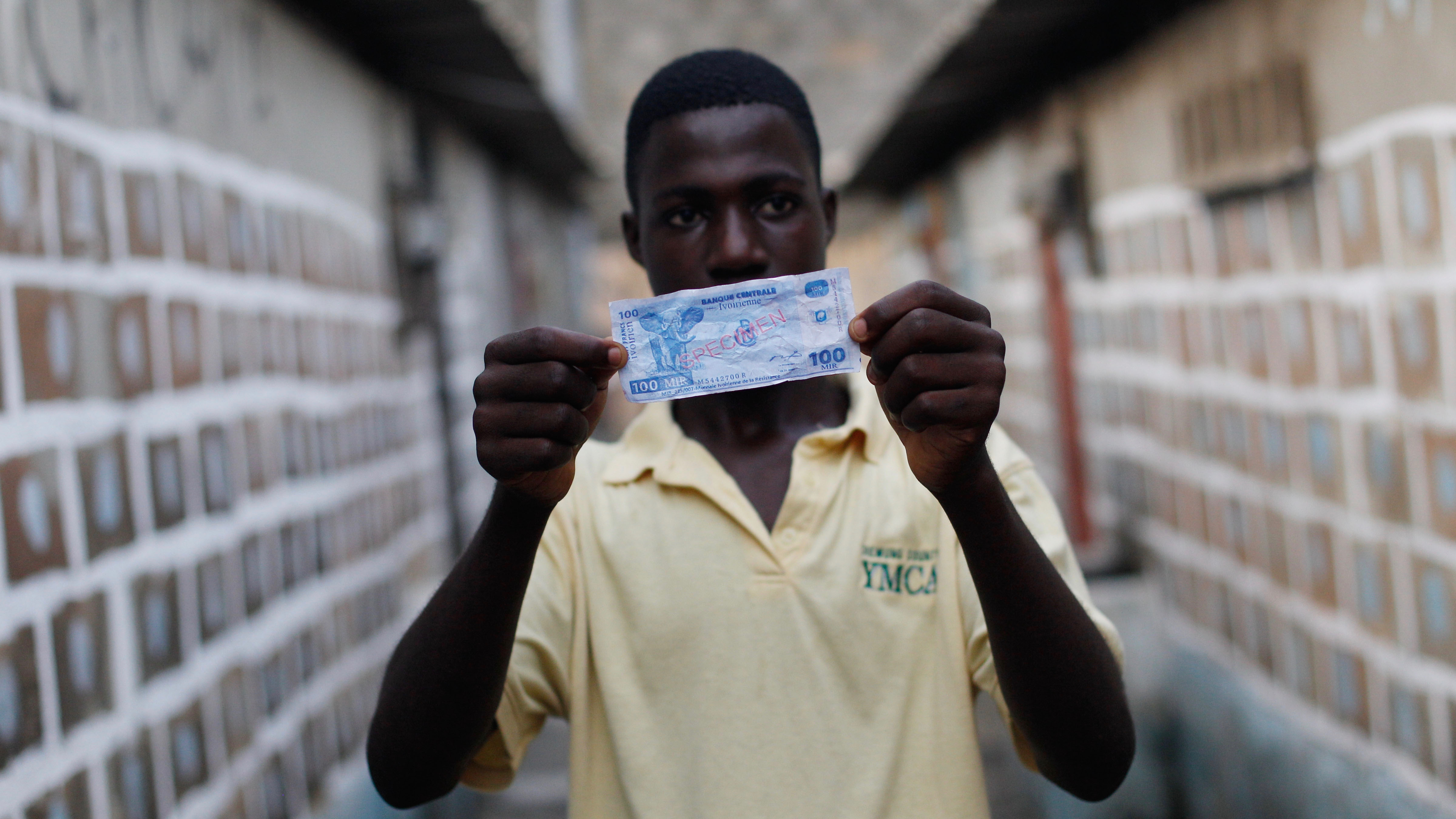 """Charley Gon, a young supporter of Laurent Gbagbo, displays a specimen 100 franc note in a fictional Ivorian currency, in the Yopougon district of Abidjan, Ivory Coast, Saturday, Jan. 8, 2011. Specimens of the """"Ivorian Currency of the Resistance"""" (MIR by its french acronym) are circulating among Gbagbo loyalists after state owned media have discussed the possibility of Ivory Coast quitting the West African franc CFA zone and establishing its own currency. The regional central bank has recognized Alassane Ouattara as the head of state and revoked Gbagbo's access to state accounts. (AP Photo/Rebecca Blackwell)"""