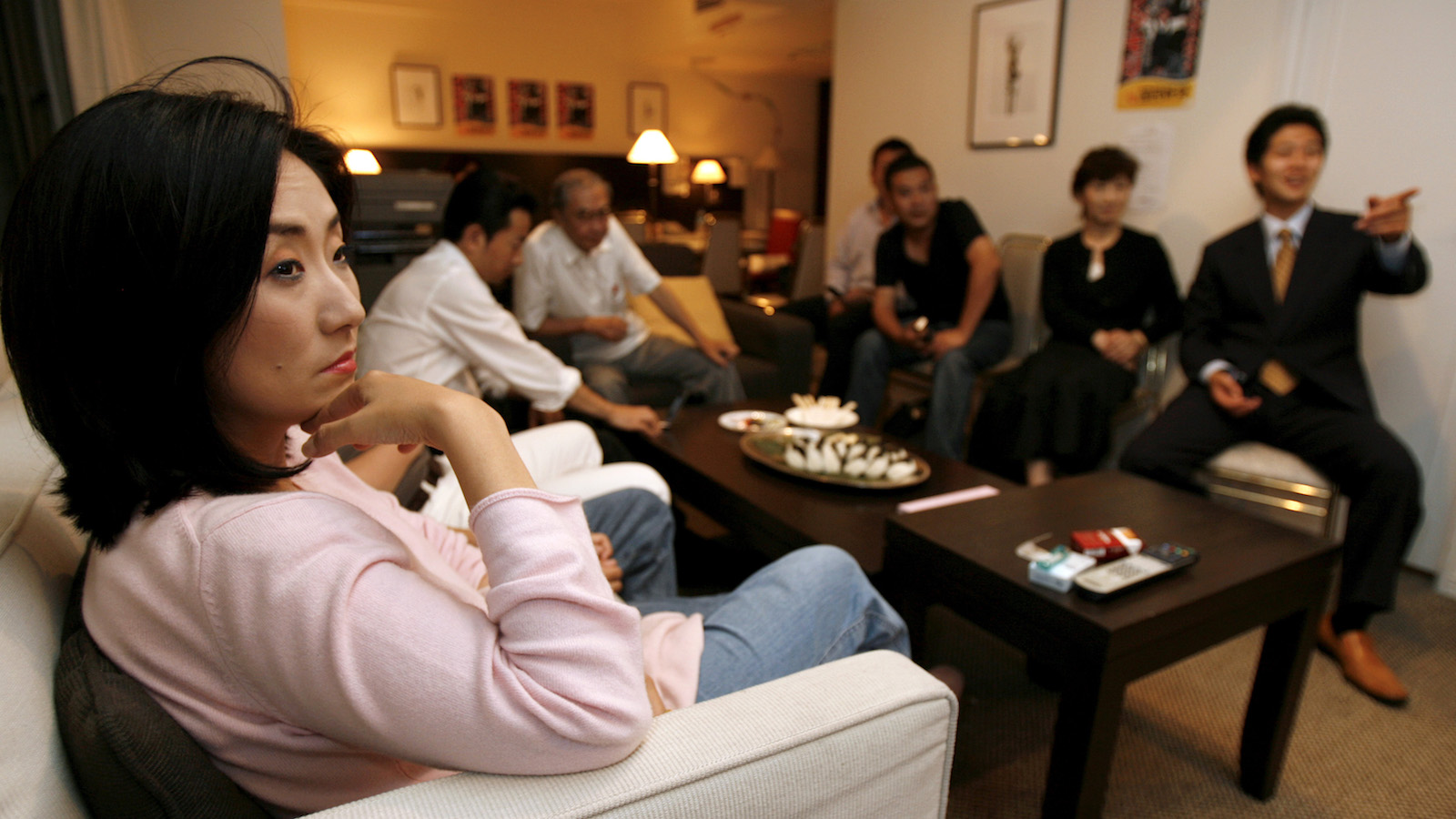 Satomi Kataoka (L), wife of former Peruvian President Alberto Fujimori who is running in the Japanese upper house election for People's New Party, waits for the result as she watches TV with Fujimori's relatives and supporters at a campaign office in Tokyo July 30, 2007. Fujimori was heading for defeat in his bid to win a seat in Japan's parliament from Chile, Japanese media said on Monday.      REUTERS/Kiyoshi Ota (JAPAN) - RTR1SD9H