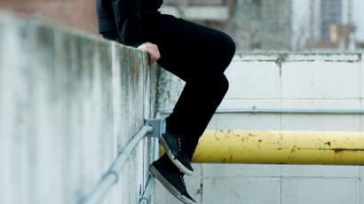 Young person sitting on a wall.
