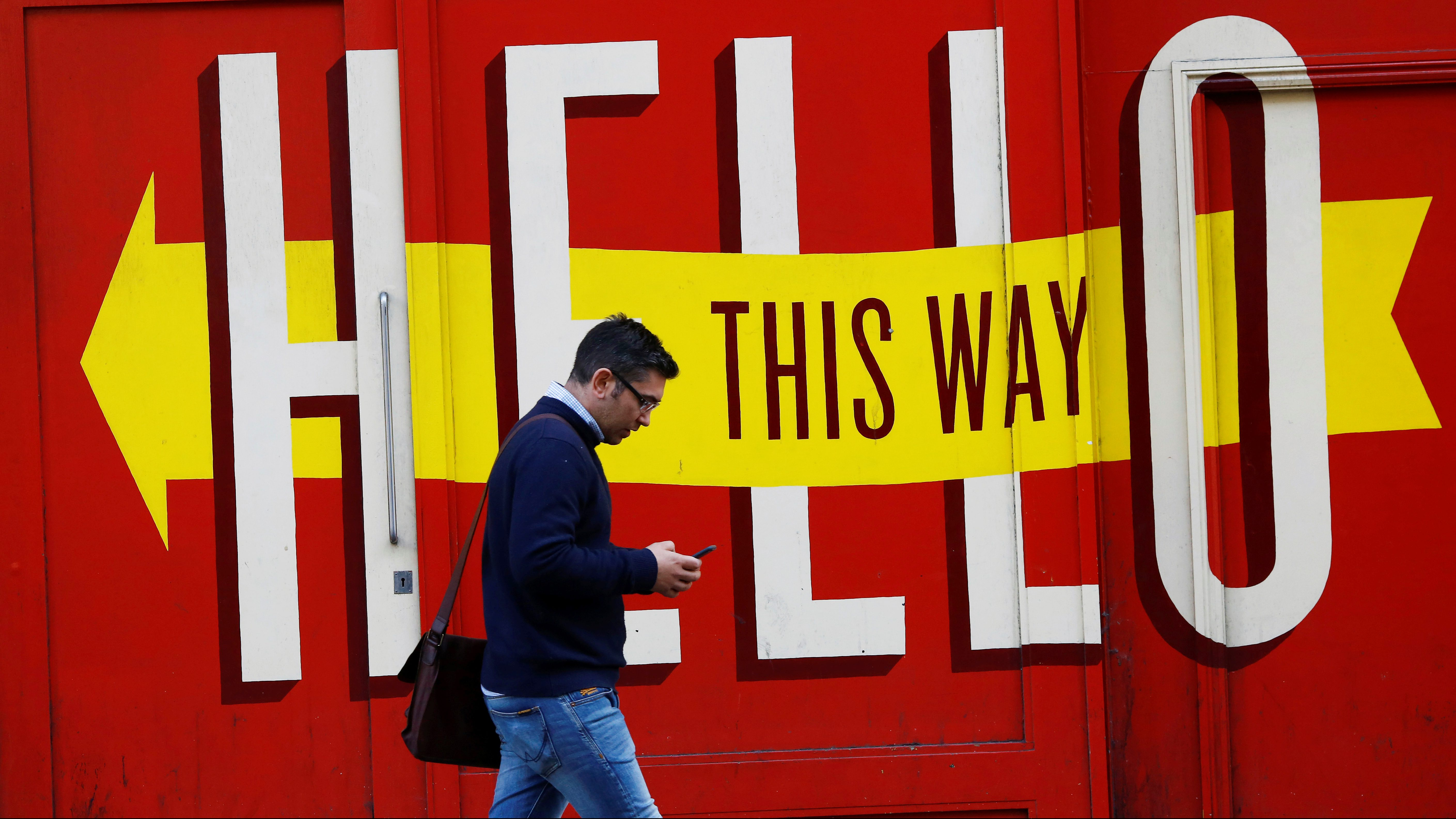 A man looks at his mobile phone in Shoreditch, London,