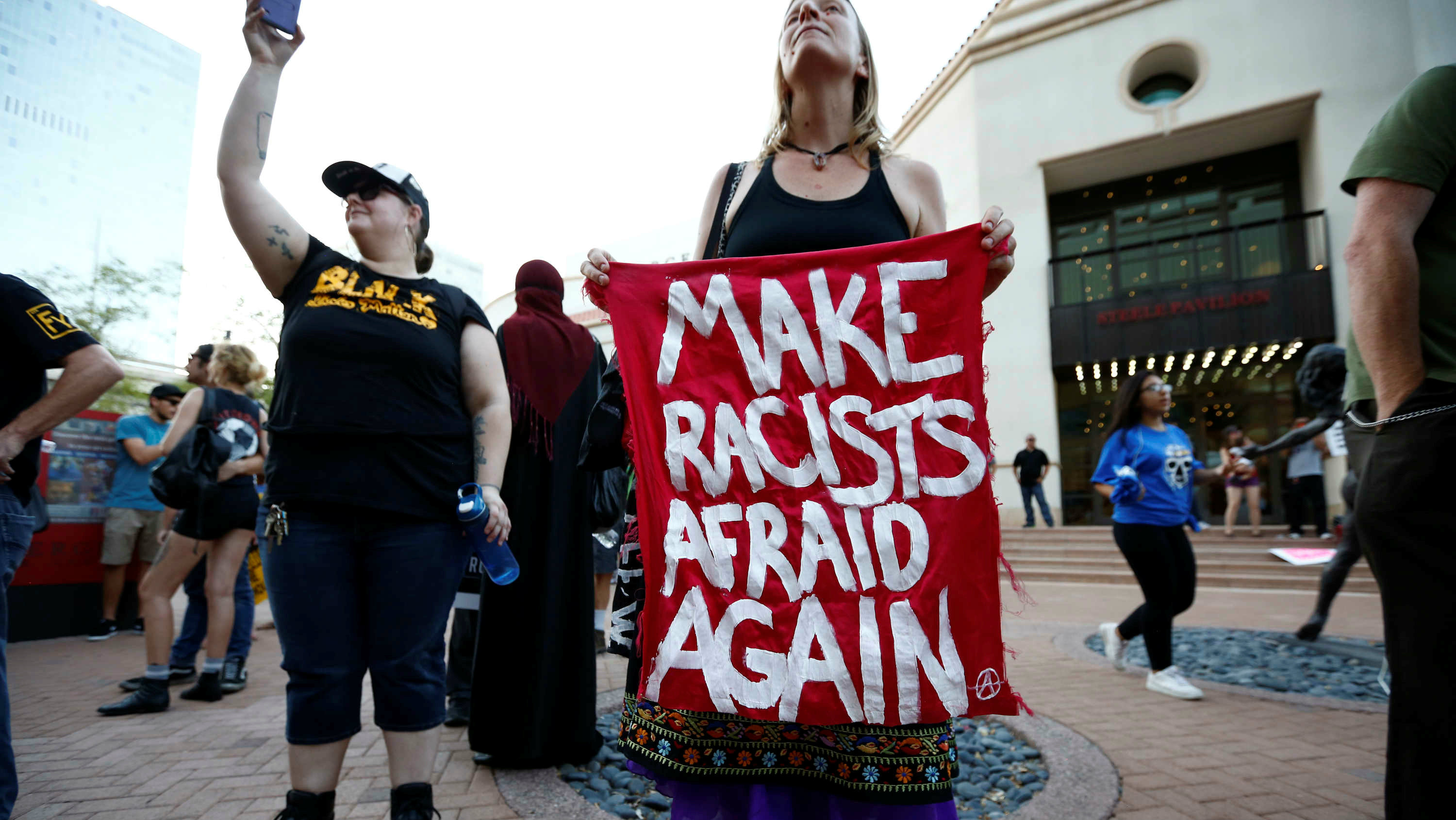 "Protestor holding sign that says ""Make Racist Afraid Again""."