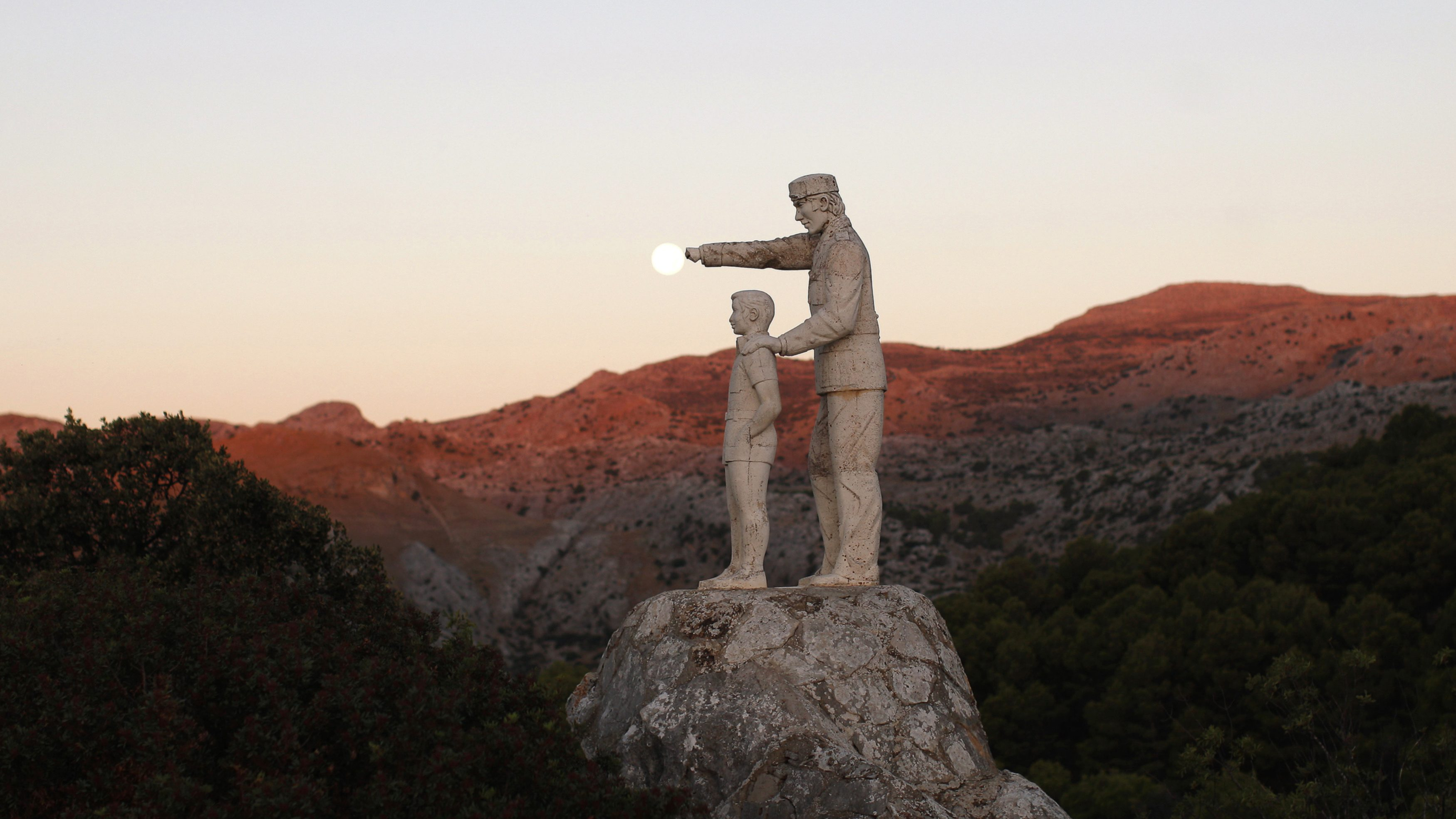 A view of statues of a man and a boy, a monument dedicated to forest rangers, as the supermoon sets over the horizon at dawn at the Sierra de las Nieves (Mountain range of Snows) nature park and biosphere reserve between El Burgo and Ronda, near Malaga, southern Spain August 11, 2014. Occurring when a full moon or new moon coincides with the closest approach the moon makes to Earth, the supermoon results in a larger-than-usual appearance of the lunar disk. REUTERS/Jon Nazca (SPAIN - Tags: ENVIRONMENT TPX IMAGES OF THE DAY TRAVEL) - RTR41XRJ
