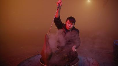 A man cooks in open air as heavy smog blankets Shengfang, in Hebei province, on an extremely polluted day with red alert issued, China December 19, 2016. REUTERS/Damir Sagolj - RTX2VONI